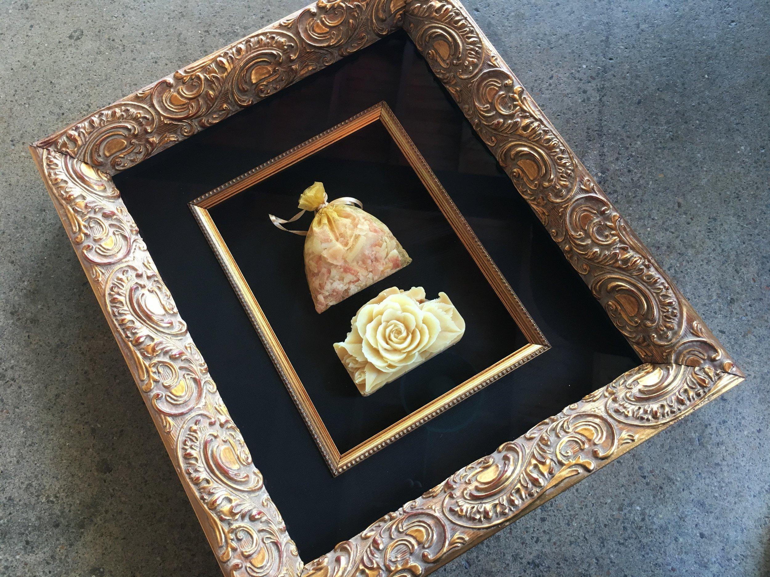 Carved soap framed. Ornate gold frame, black silk matting and a gold fillet trim