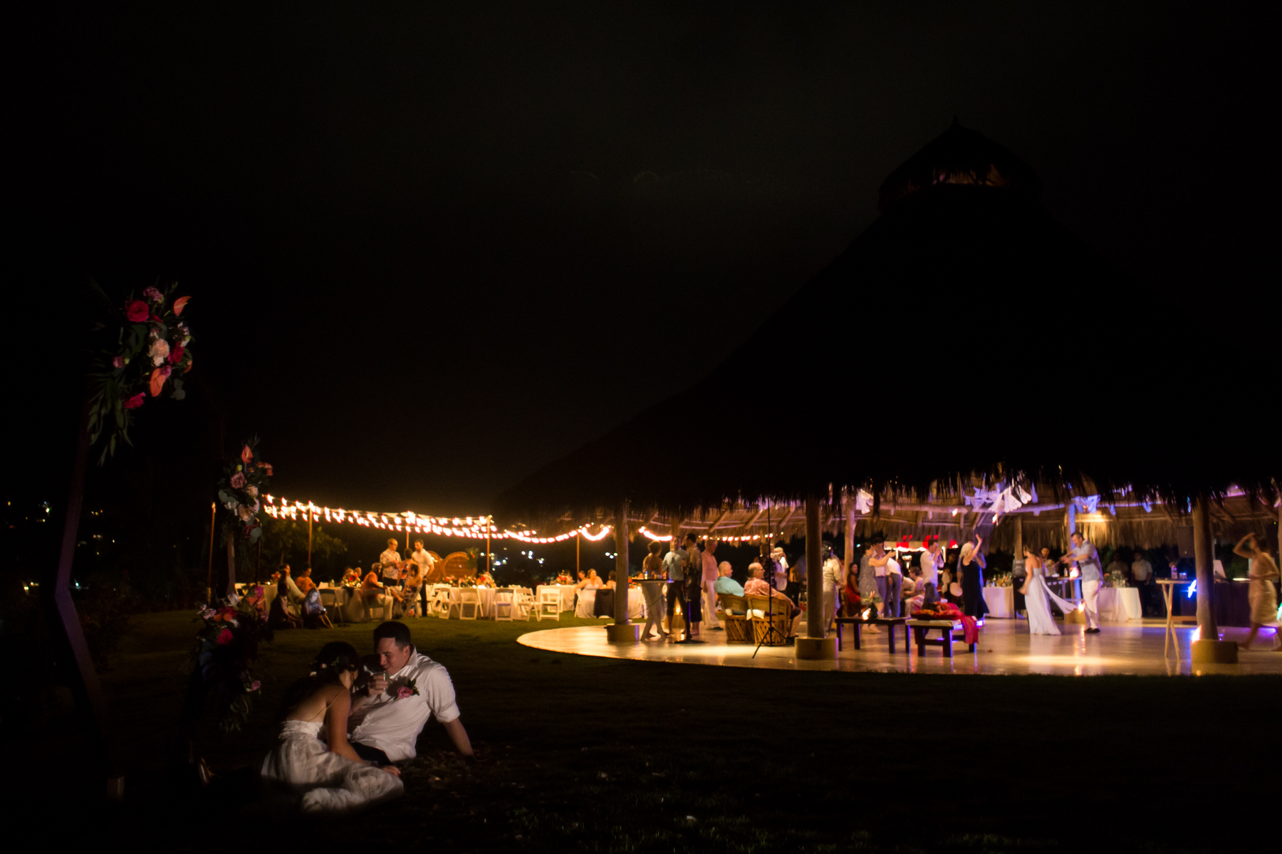A bride and groom sit outside the palapa while their reception goes on. Photo by Erin Parker.