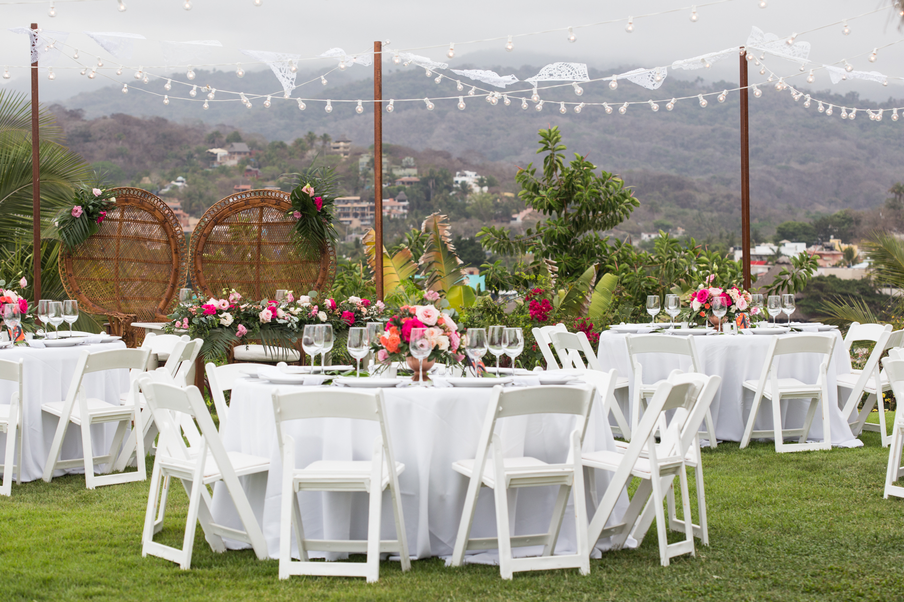 Circular tables for guests and a sweetheart table for the bride and groom with wicker peacock chairs. alternative dinner table setup photos are here