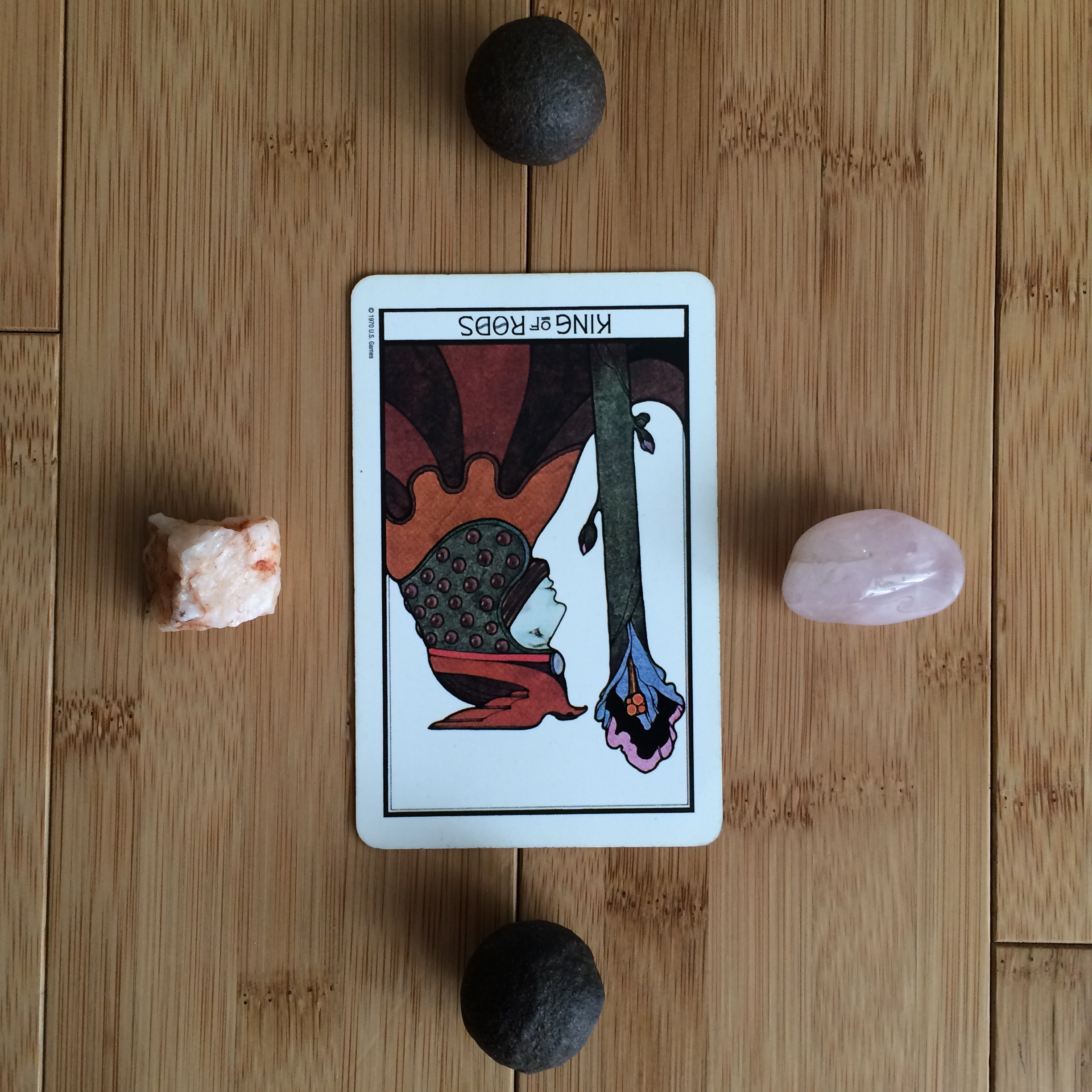 Kings of Rods reversed from  Aquarian Tarot Deck . Stones clockwise from left: unrefined quartz, moqui ball, rose quartz, moqui ball