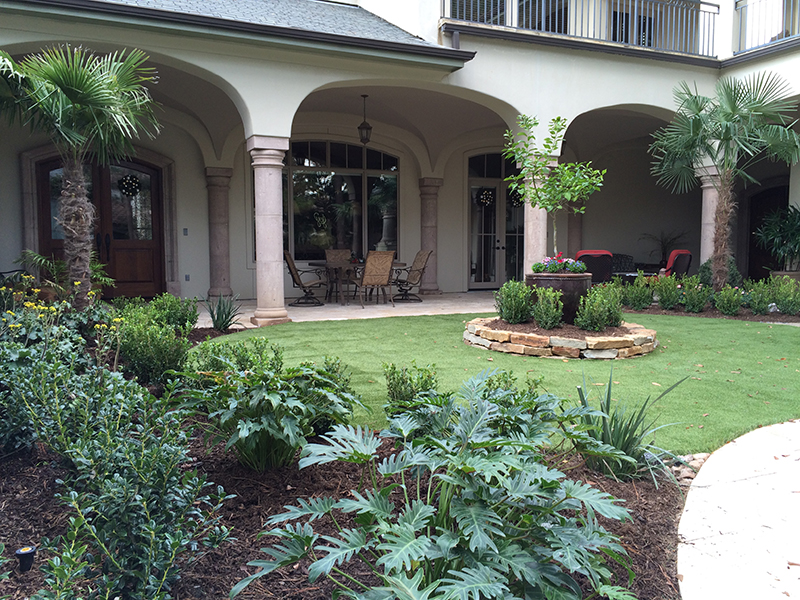 Tuscan-courtyard-palm-tree-boxwood-flax-lily-moss-rock-stcaker-stacked-wall-urn-lemon-tree-ligularia-xanadu-synthetic-artificial-turf-grass-custom-design-The-Woodlands-houston-spring-cypress.jpg