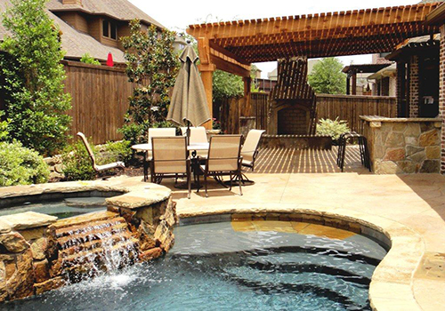outdoor-arbor-pergola-fireplace-patio-pool-flagstone-custom-design-build-pool-builder-waterfall-covered-deck-decking-landscaper-company-pools-the-woodlands-magnolia-houston-cypress-montgomery-conroe-tomball.jpg