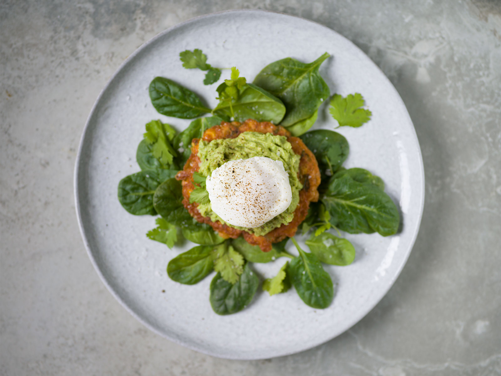 Sweetcorn Fritters, mashed avocado and salad, topped with a poached egg