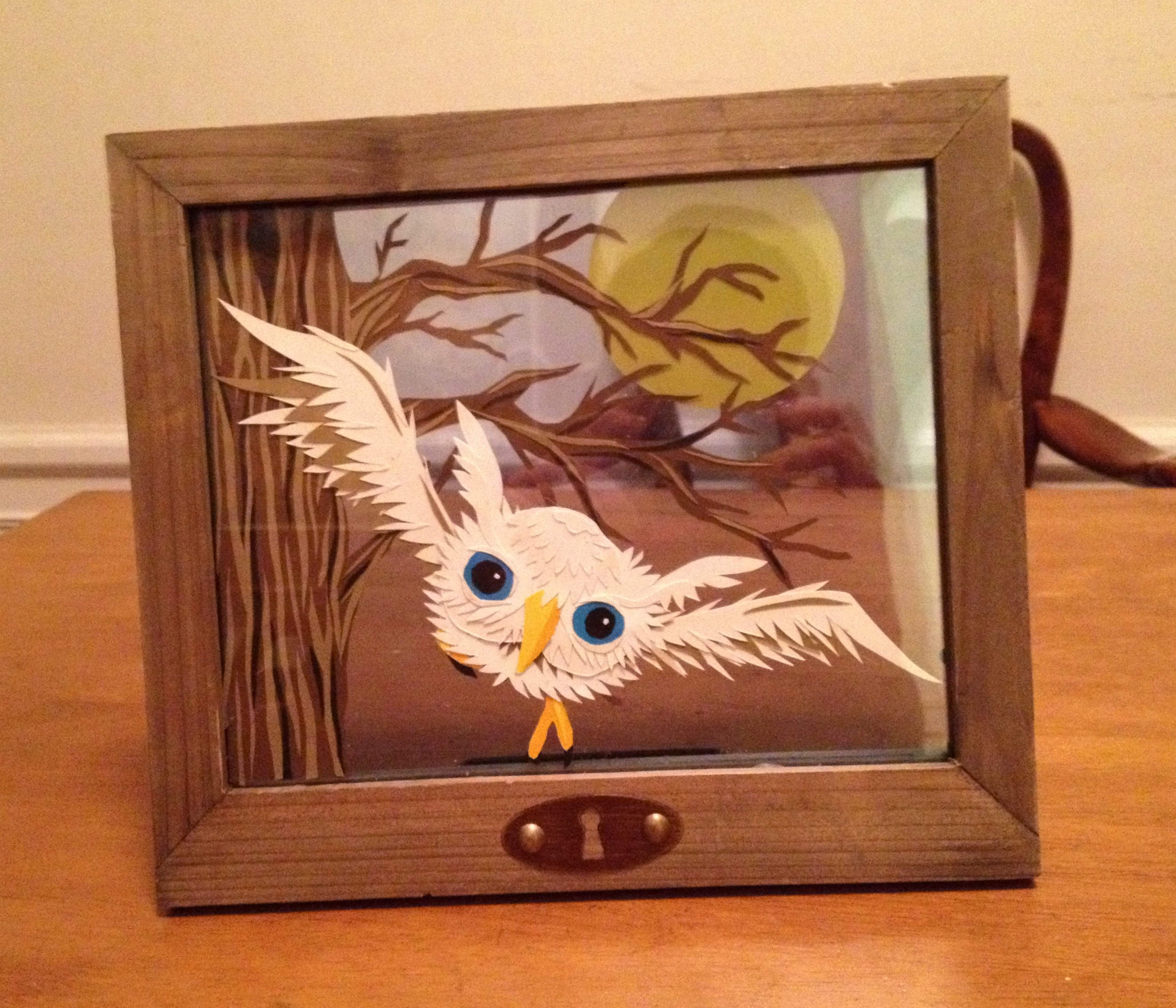 """Jeffrey"", this owl piece is made of cut paper, glass, wood, and glue."