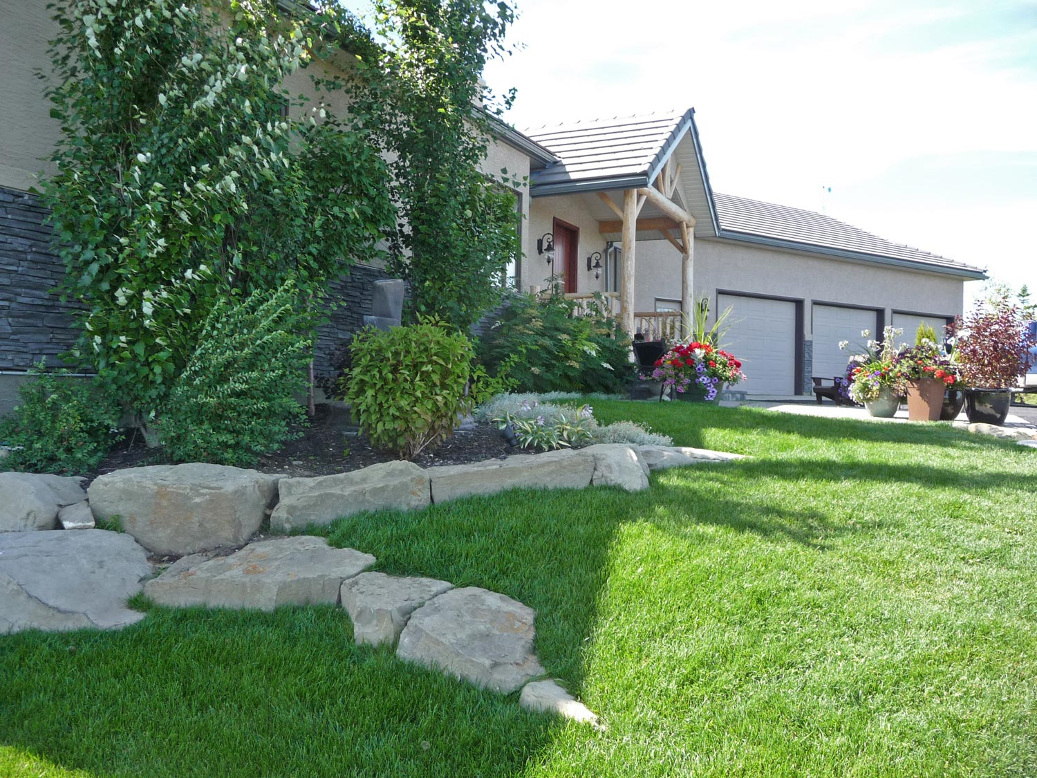 stone boulder retaining wall and landscaping