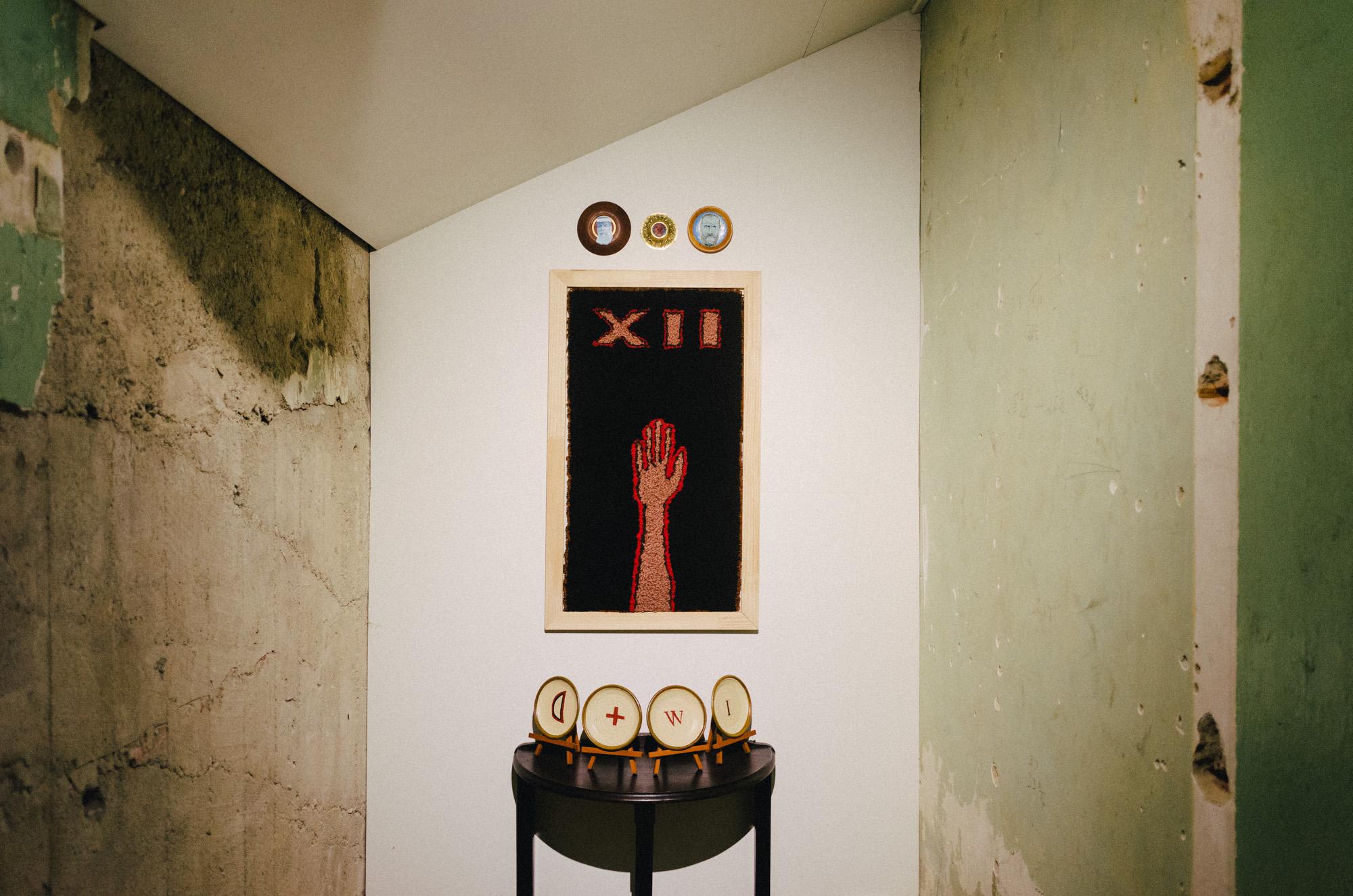 Ringatū  2015  Wool  92 x 54 x 3cm framed  alongside  Te Wepu (installation)  2013  Acrylic on ceramic plates  Dimensions vary