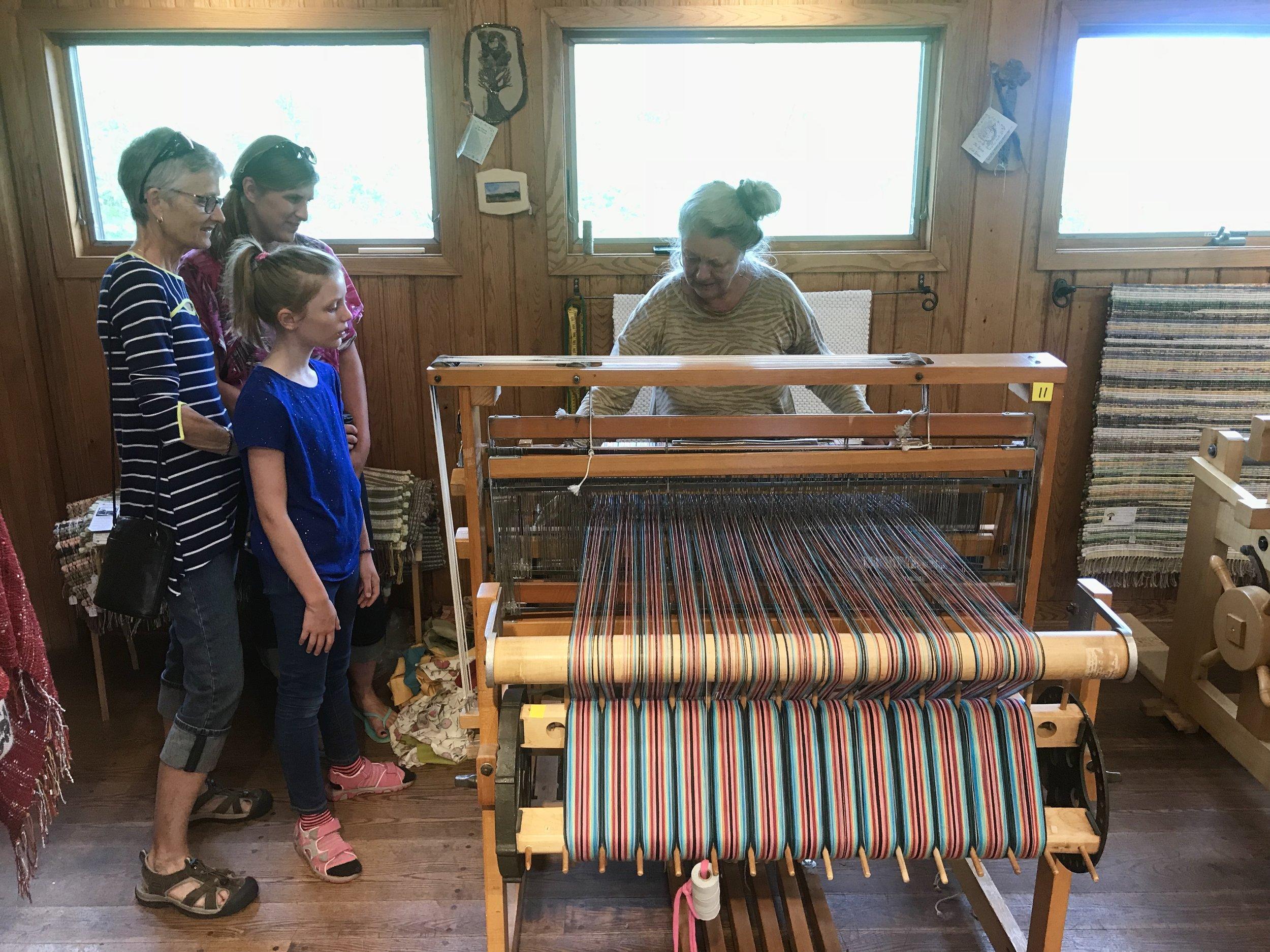 Susan Sabre weaves a rug as patrons watch this impromptu weaving demonstration.