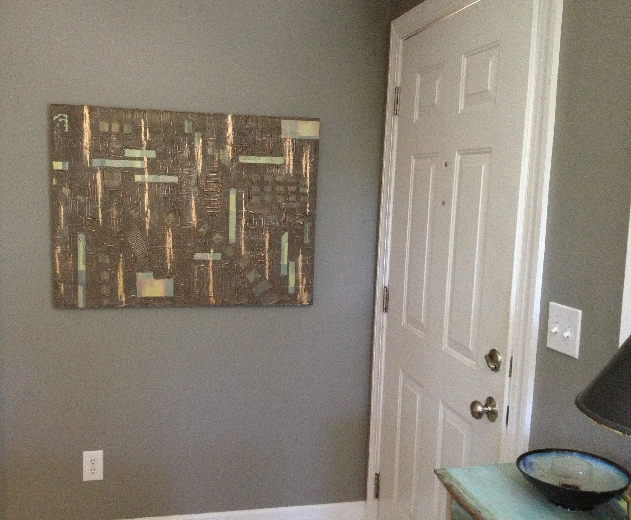 Shown hanging horizontally on a gray wall.