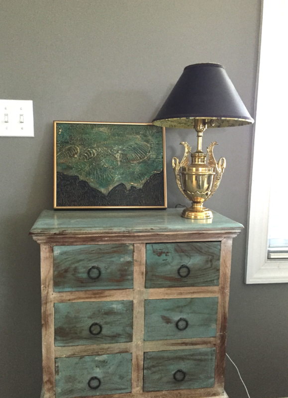 Shown framed in room setting on small decorative chest.