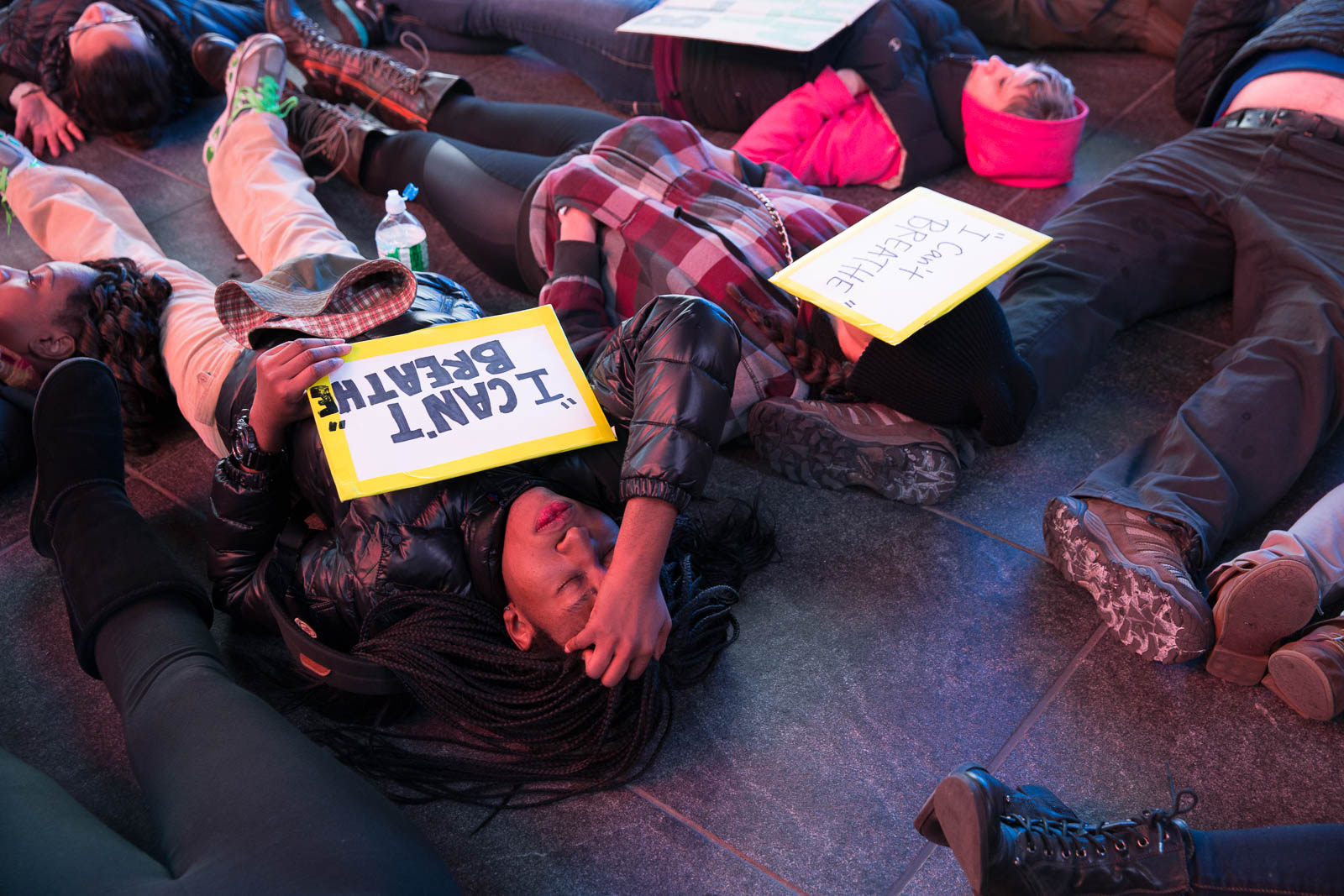 "A woman lies down on the ground for a mass ""die-in"" in Times Square."