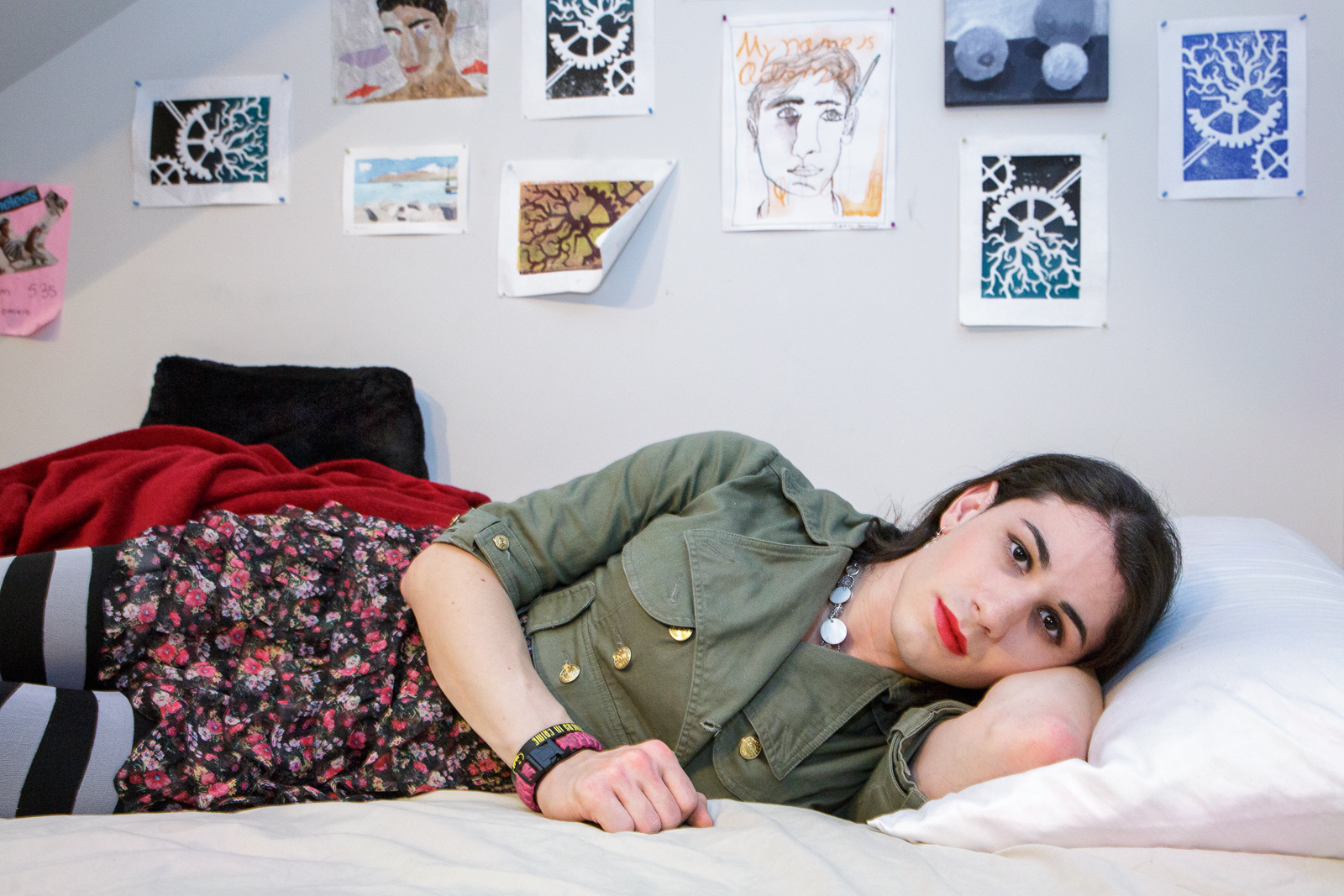 Ashley lies on her bed, in front of drawings she made as a young boy.