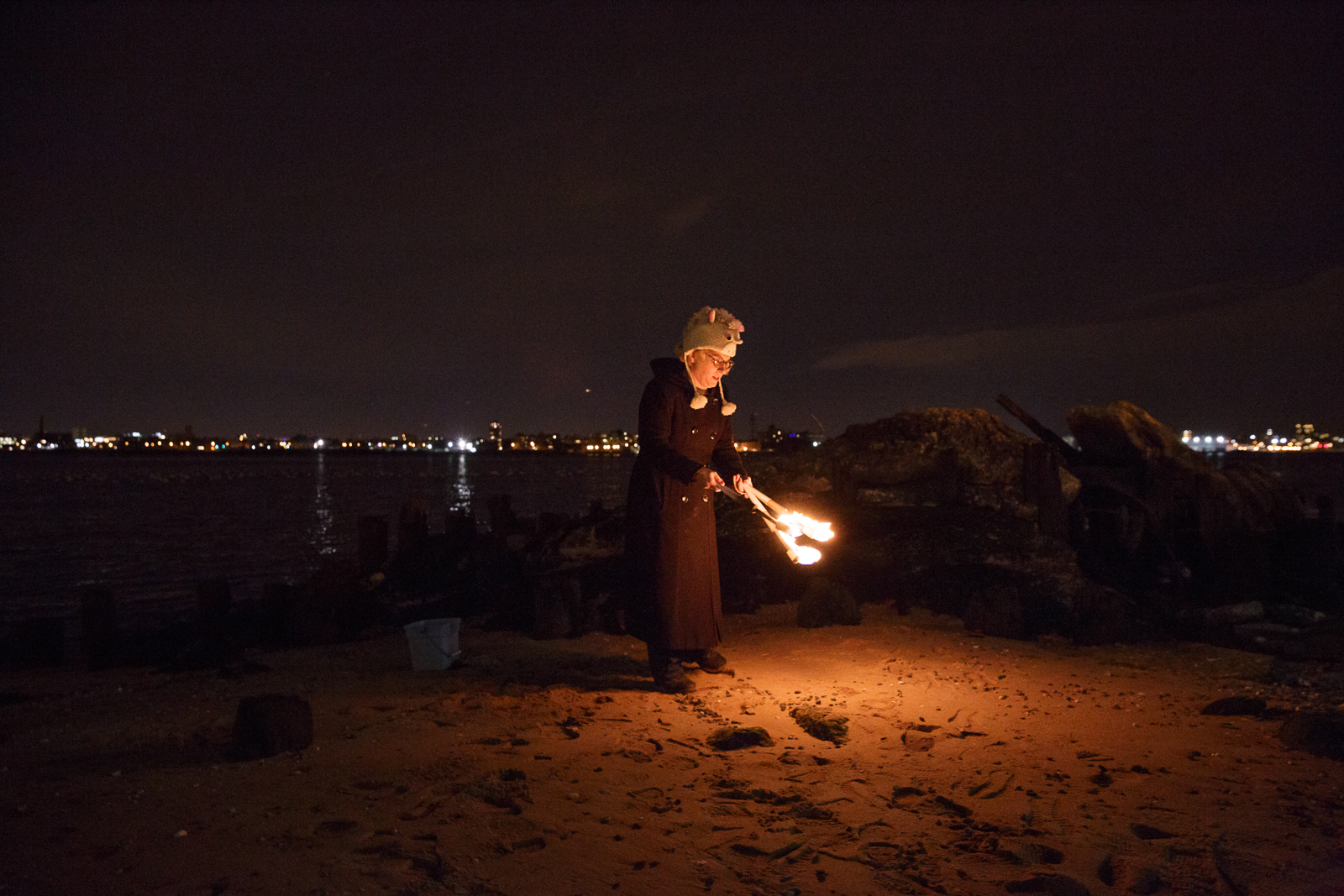 Kylie holds flaming torches, attempting to juggle them on the East River. Juggling flaming torches has been a dream for her since she was in middle school.