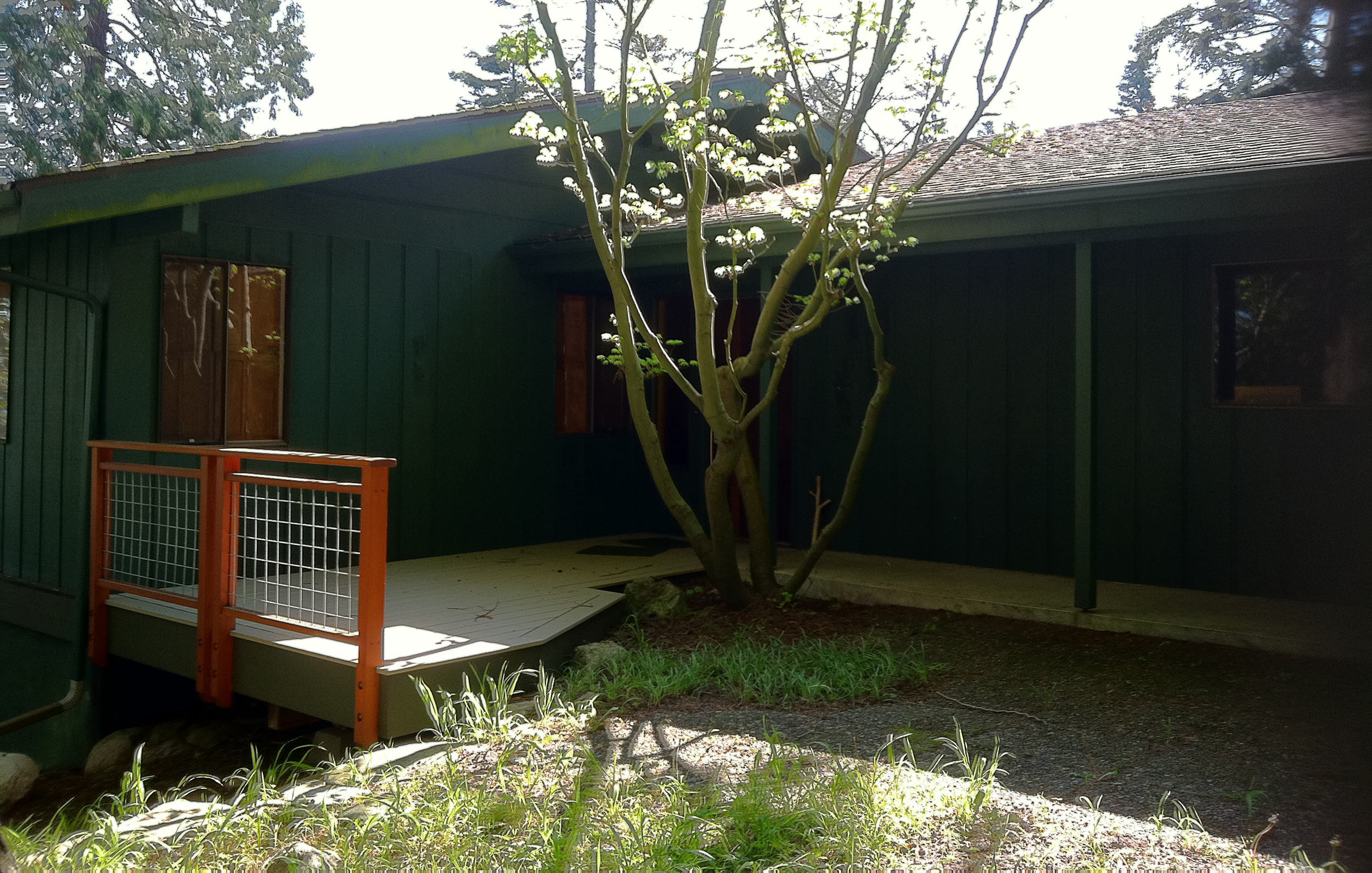 Before picture of home entry- T-111 siding with mold, old fashioned aluminum windows, no trim. Deck new from phase 1......
