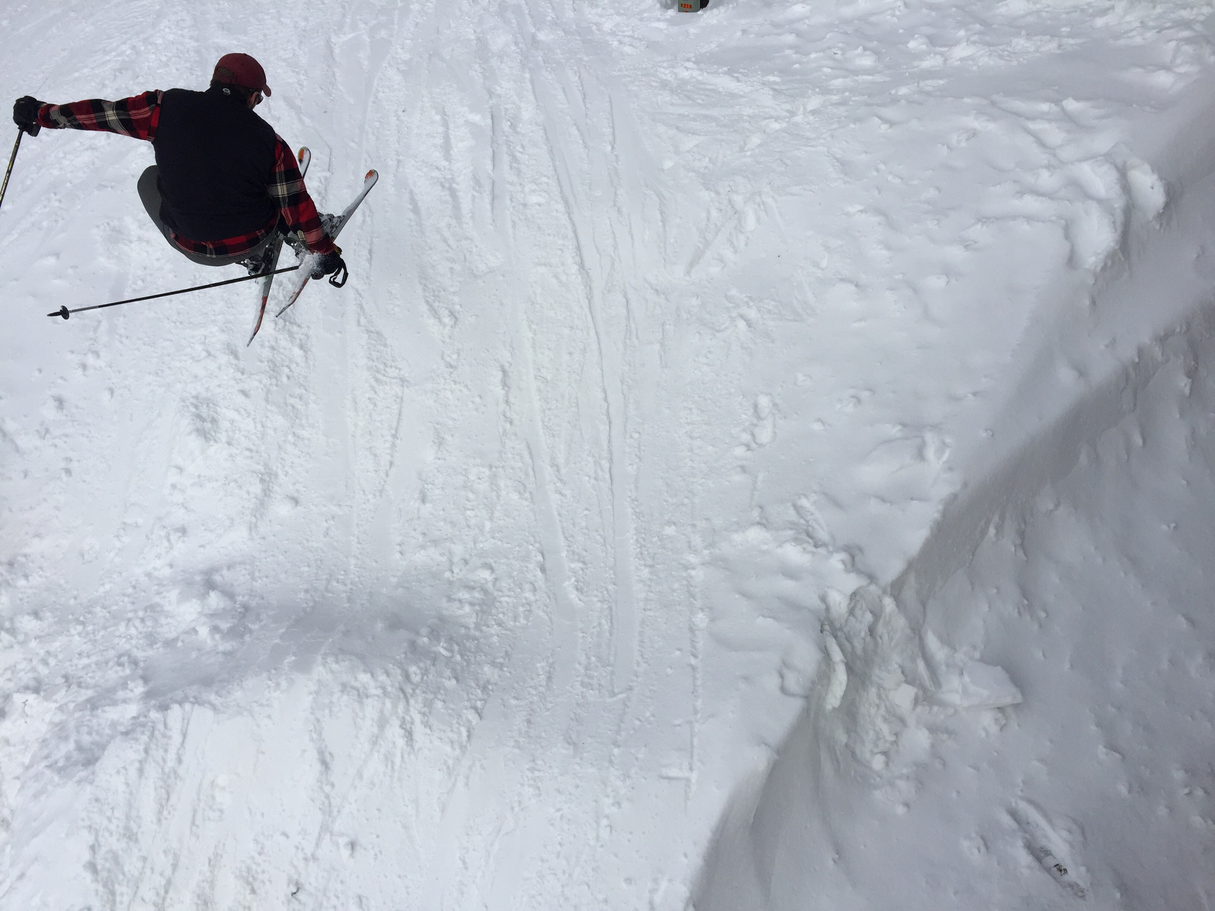 Image taken on a deck while skier jumps below.