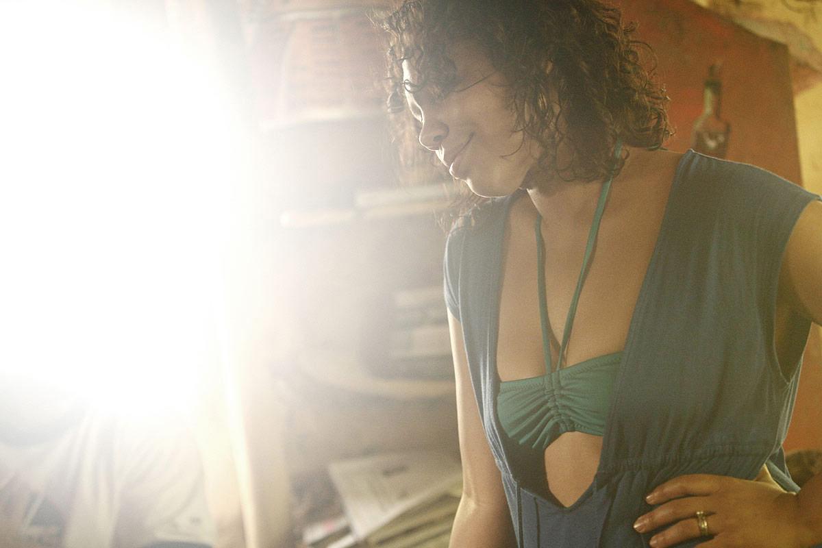 A woman soaks in the sun through a window.
