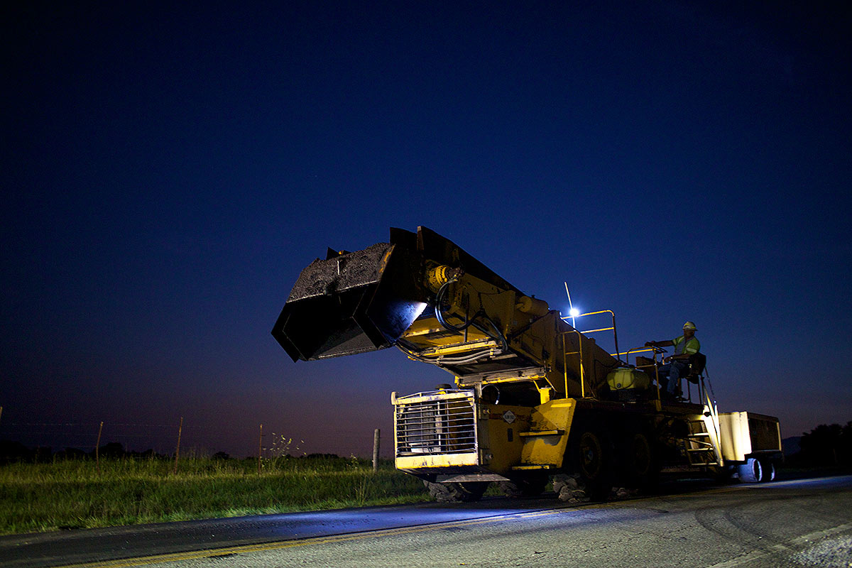 Night paving work using Caterpillar heavy machinery.