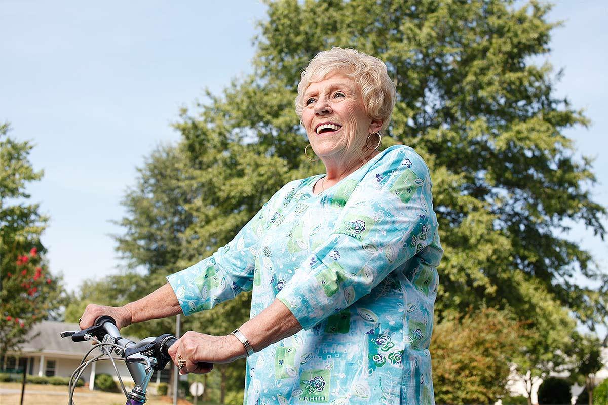 An older woman in retirement enjoys a bike ride.