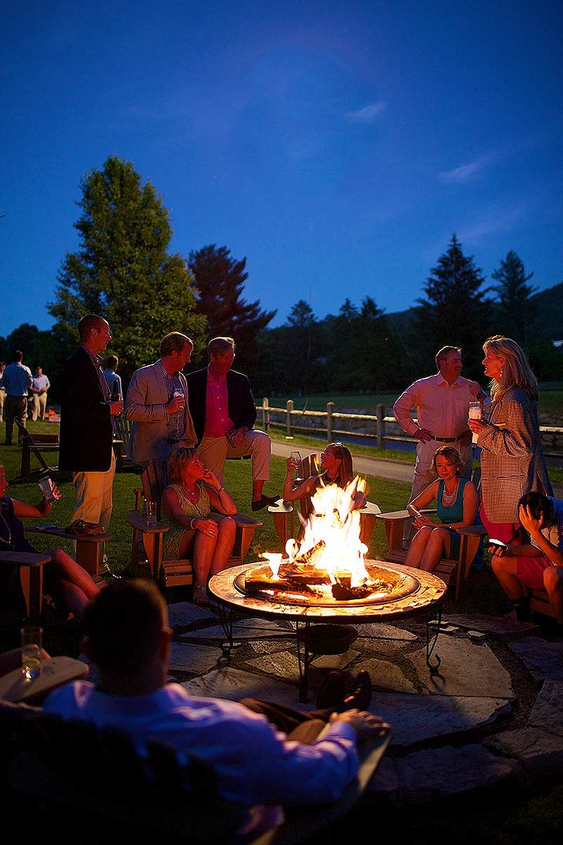 A group of people gathered around a fire pit at a party at the Greenbrier.