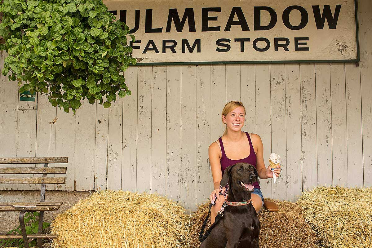 A young girl enjoys ice cream with her dog at a small town farm store.