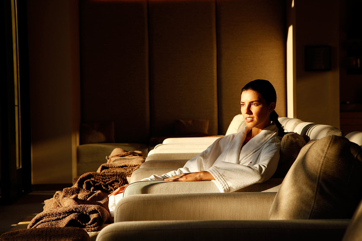 A woman sits in a spa with the sun coming through the window.