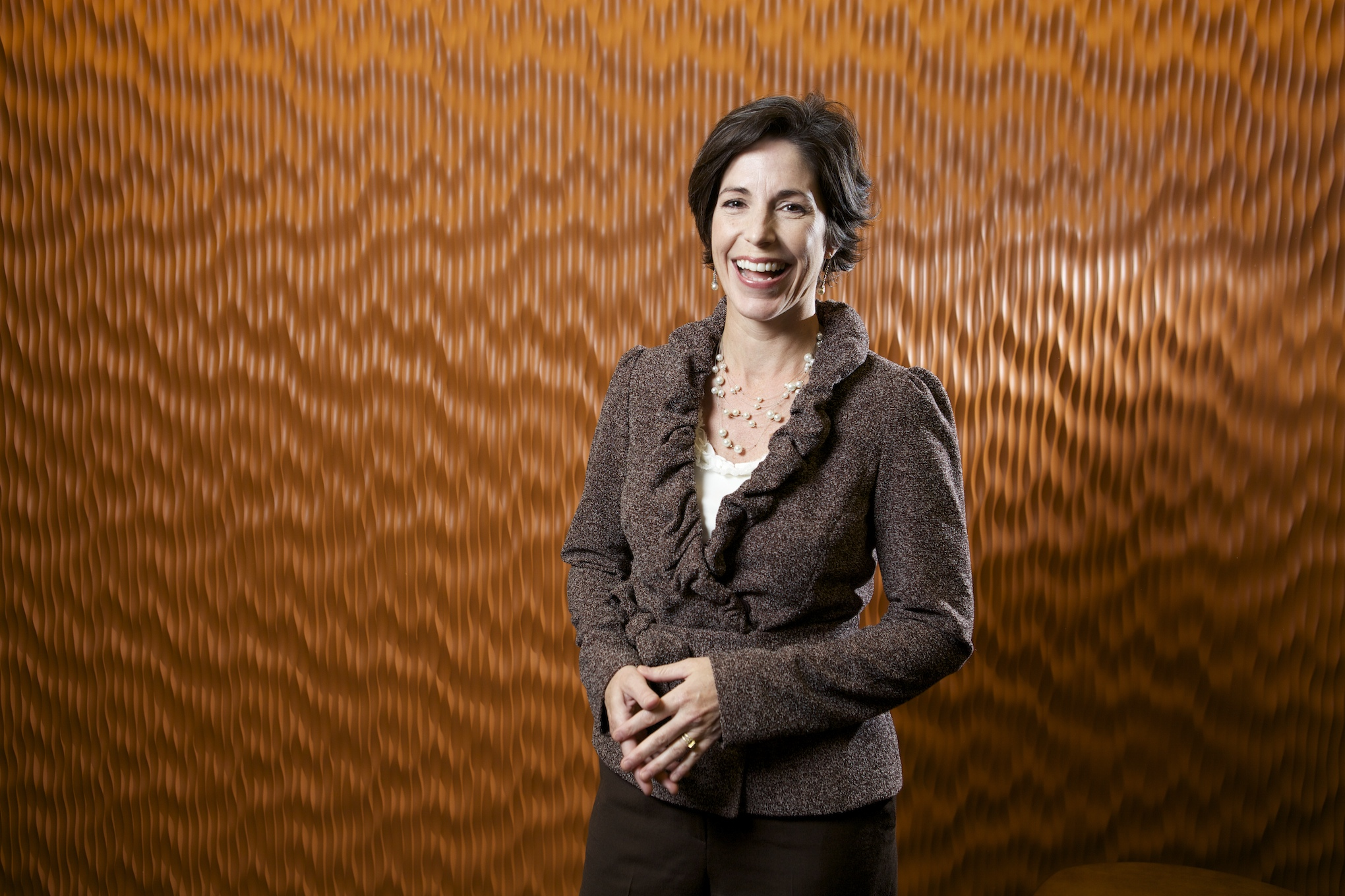 A female executive stands in her office for a corporate headshot.
