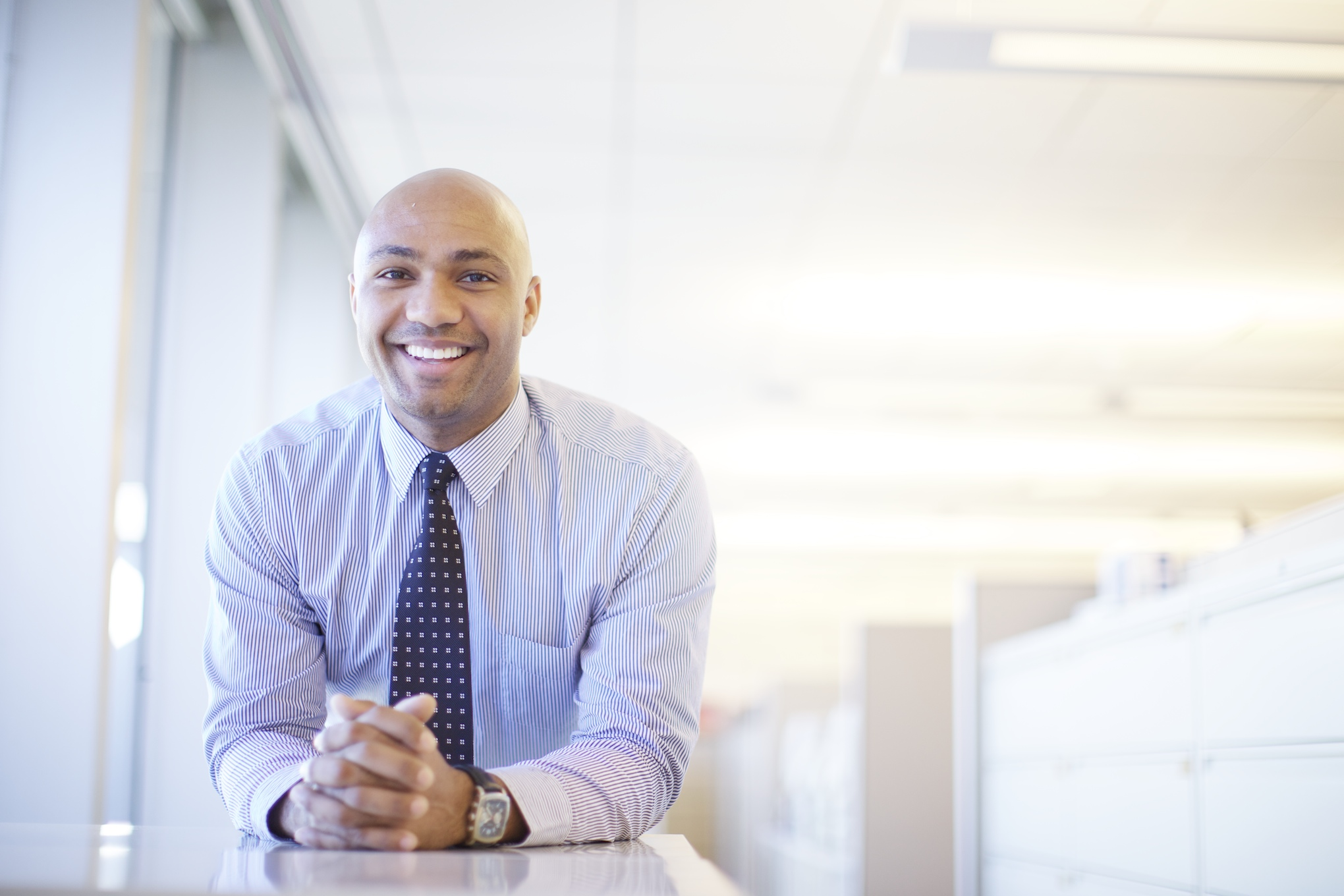 An corporate professional stands for an environmental portrait in his office.