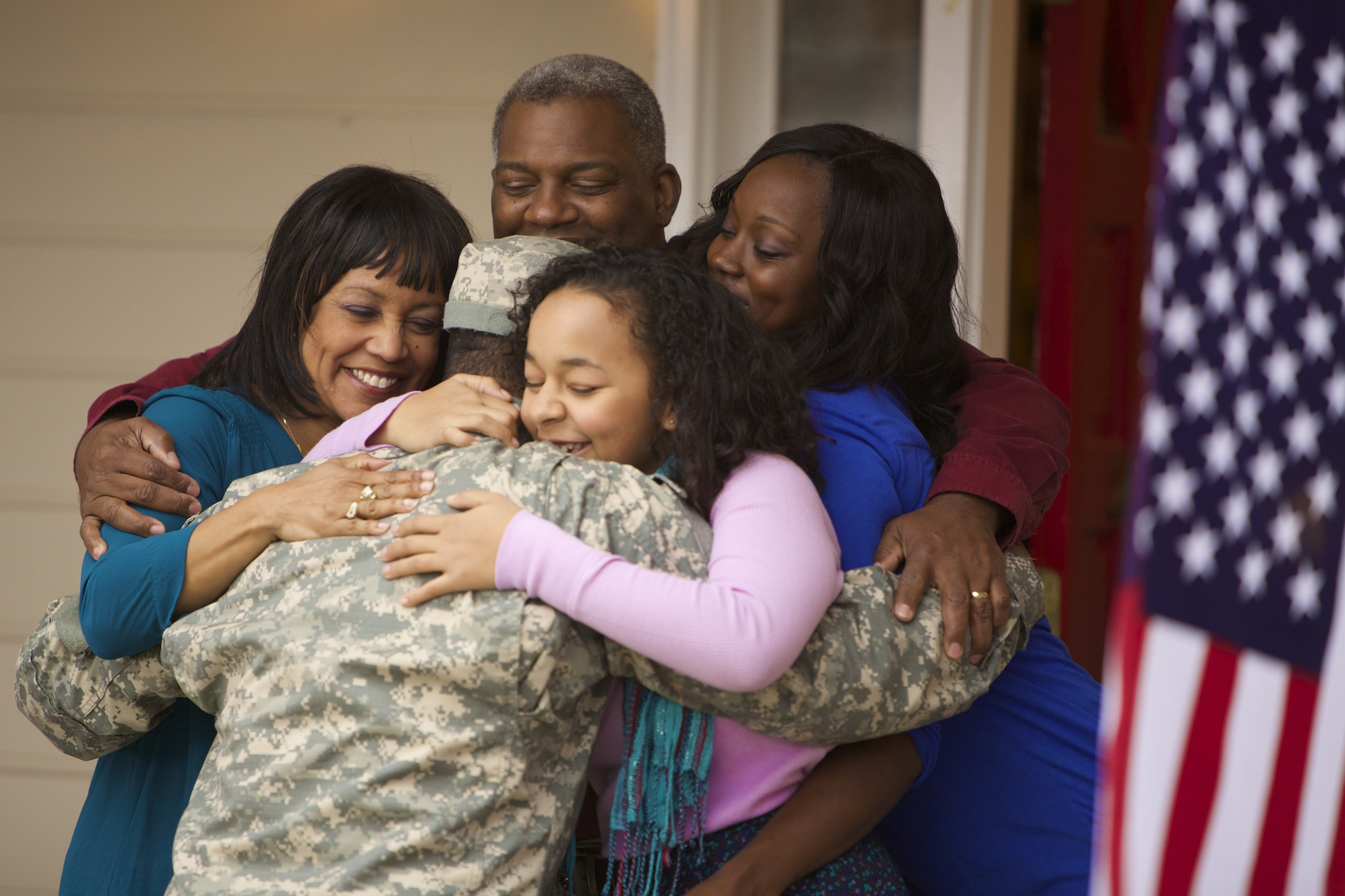 A Serviceman hugs his family on the front porch as he returns home.
