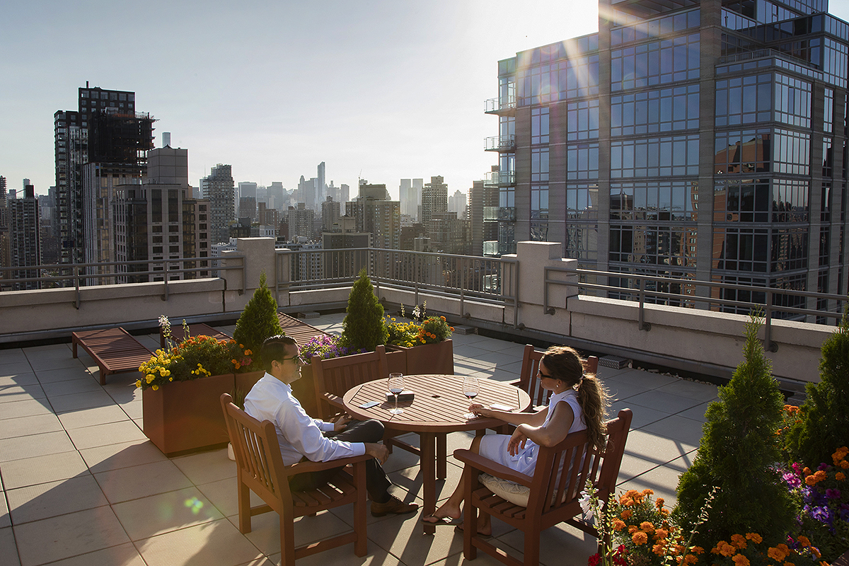 Photograph of two people enjoying a glass of wine on a rooftop in New York City.
