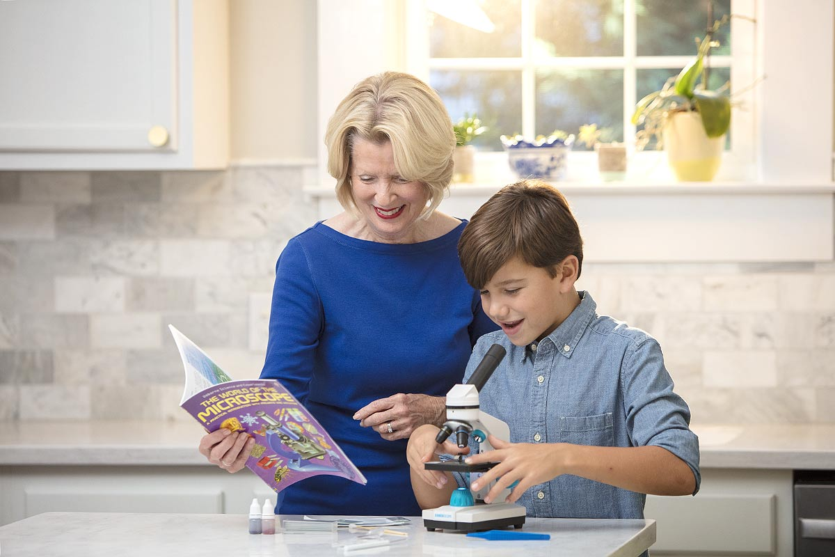 Grandmother helping her grandson in the kitchen with a microscope.