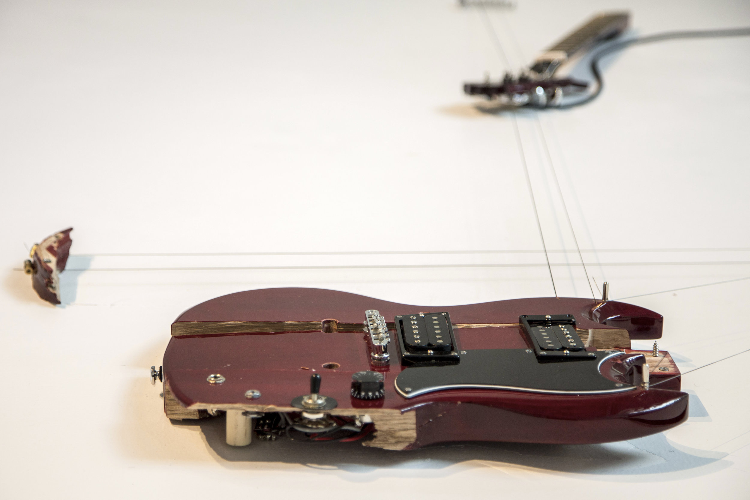 "Melody of Certain Damage #10, 2018, detail, broken electric guitar, strings, microphone, screws and amplifier, 73"" x 41"" x 3"". Image by Loló Bonfanti"