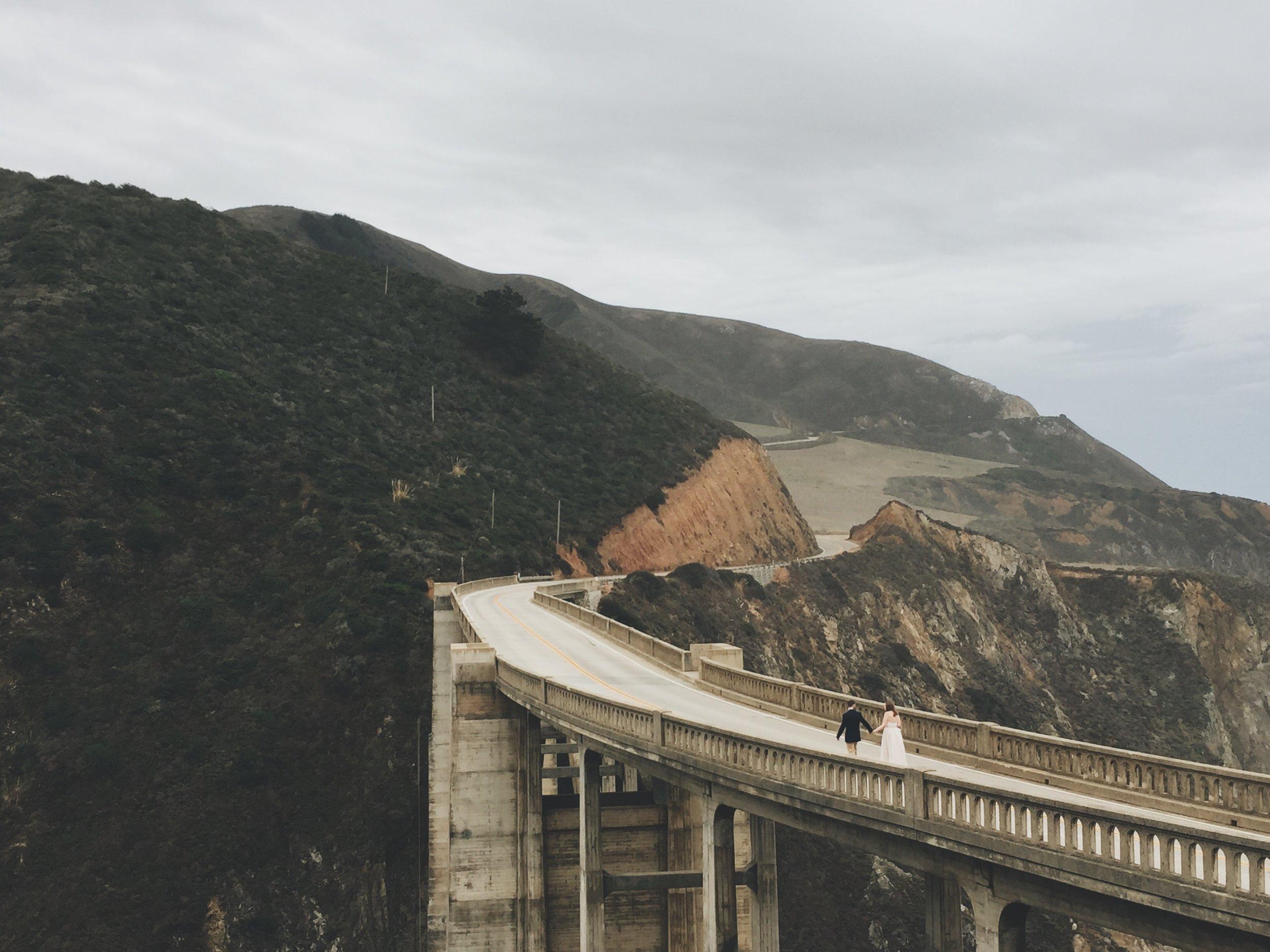 Sarah Rotrock and Ricky Stephens walking down Bixby Creek Bridge in Big Sur California
