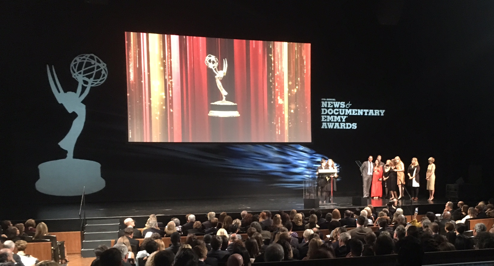 THE WHOLE TEAM ON STAGE WITH AS KIRSTEN ACCEPTS THE EMMY