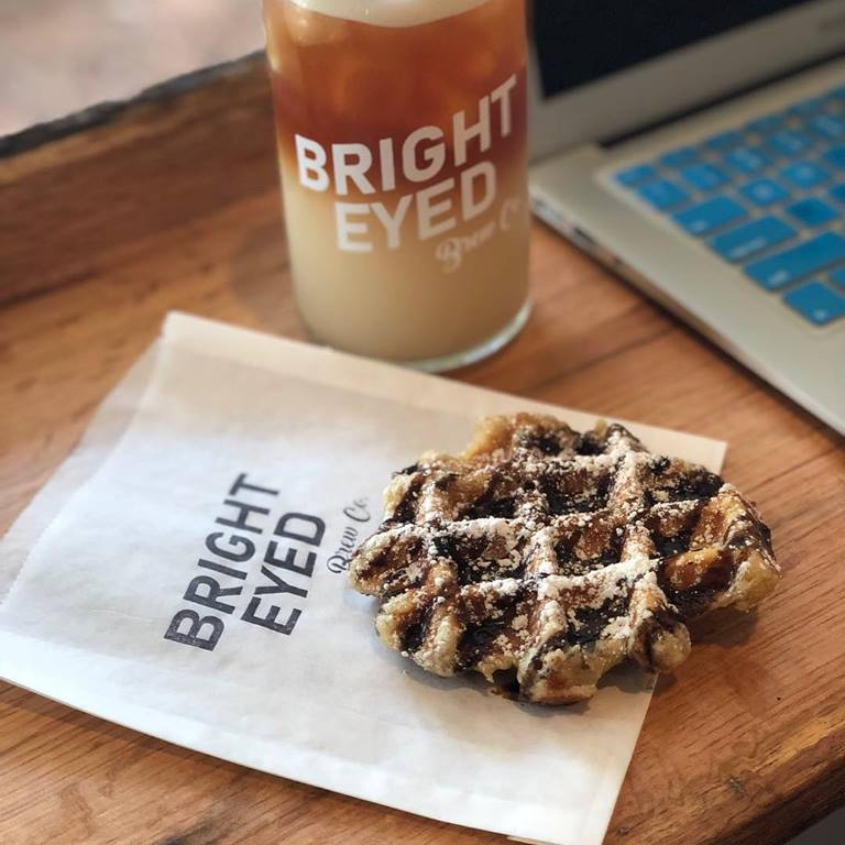 Bright-Eyed Brew Co.  623 Washington Ave. Ocean Springs, MS 39564  Bright-Eyed Brew Co. is known as THE place to get nitro-brew and cold brew coffee on the MS Gulf Coast! They also serve specialty Belgian waffles! Owned and operated by a charming husband and wife team, Bright-Eyed is sure to lift your spirits! Pictured above is an iced chai-chatty and a liege waffle with dark chocolate and powdered sugar…we're drooling already!