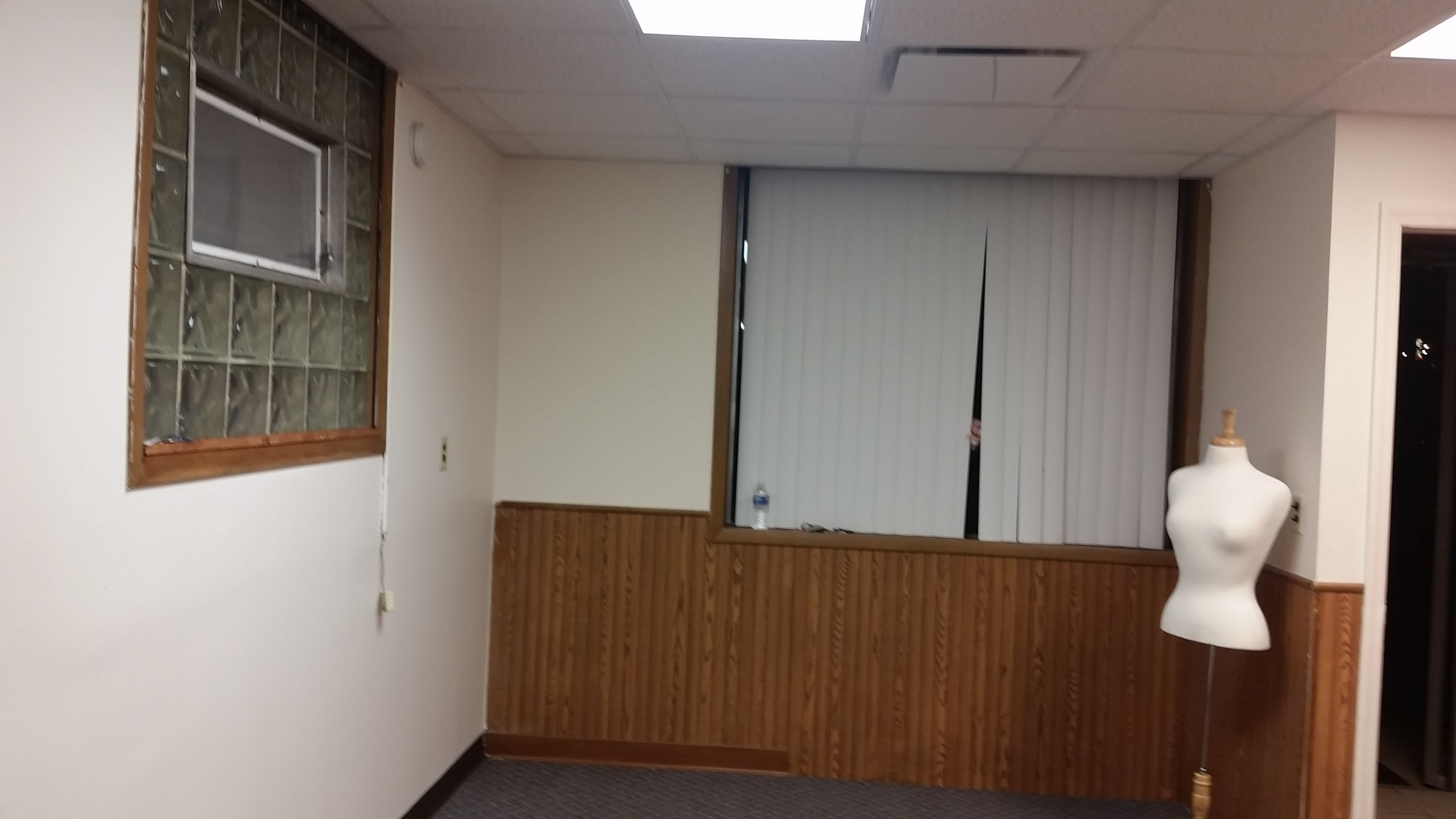 Here's a before.  Glass block windows, vertical blinds and paneling.  Says office, not boutique.