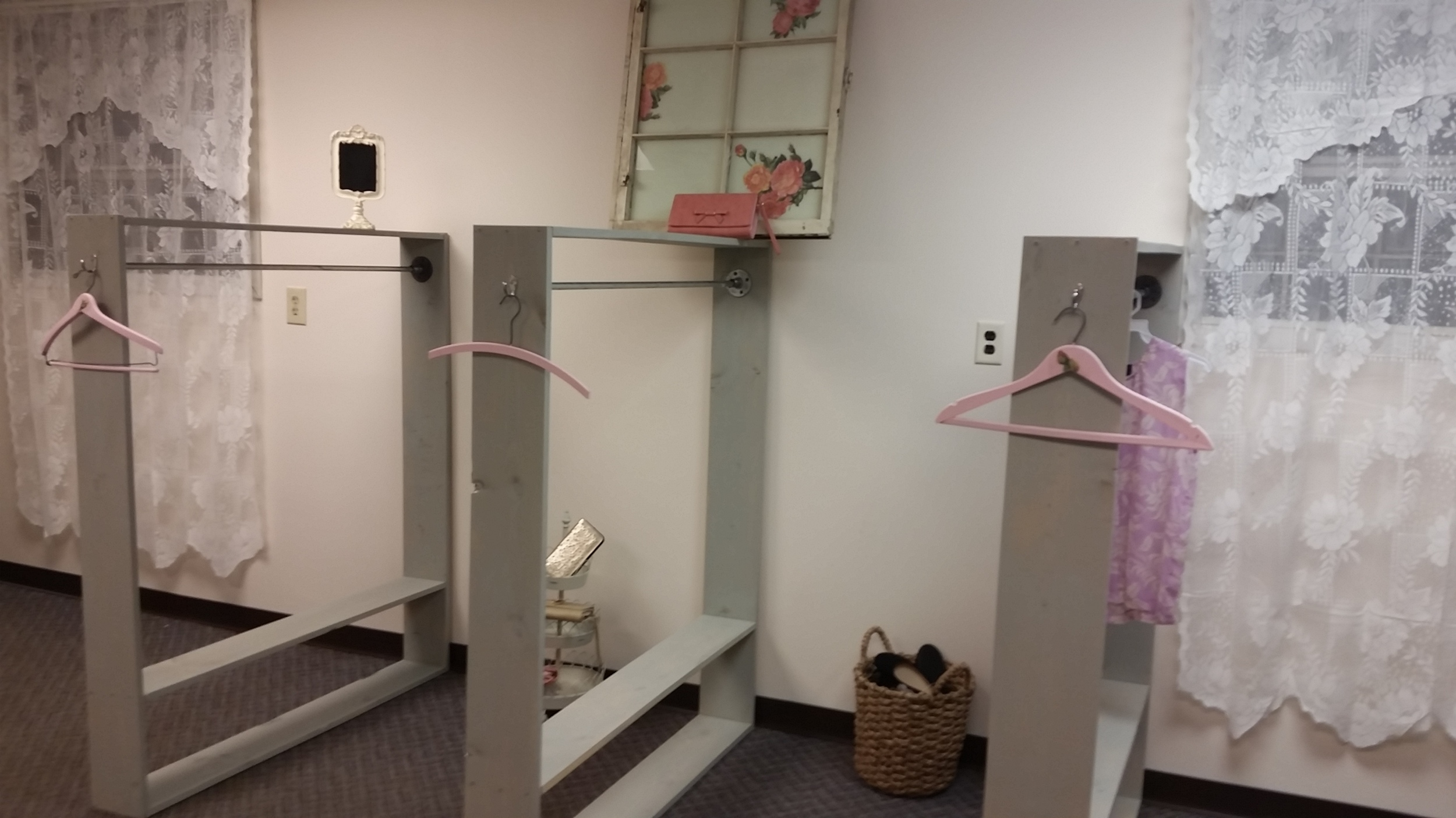 Wooden racks with galvanized pipe fittings and conduit, painted out in gray provided the racks needed for clothing.  Vintage wooden hangers painted pink and decoupaged with floral images provide a place to showcase special outfits.