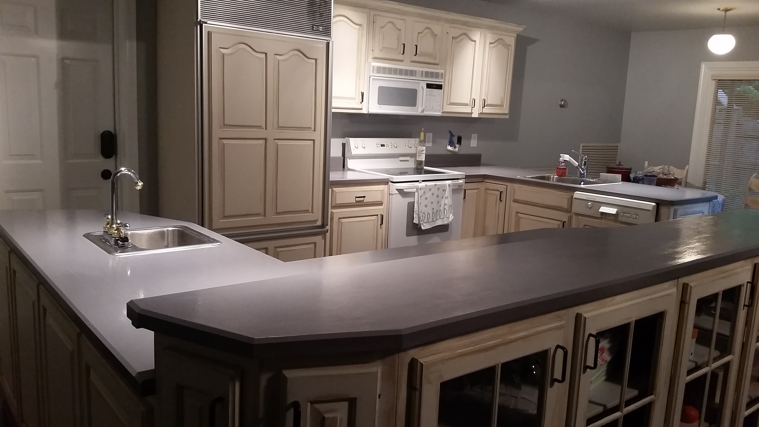 Here's an after shot of the painted kitchen.  The previously dark cabinet in the foreground is painted to match the rest of the cabinets, as well as the dark trim above the back cabinets.  This gives the whole space a more open feeling.  The counters were painted with Gray.  Some glitter was added in for subtle shine and then multiple layers of polycrylic.  The homeowner has since updated her faucets to the same oil rubbed bronze color the cabinet door pulls were painted.  They were previously chrome and gold.