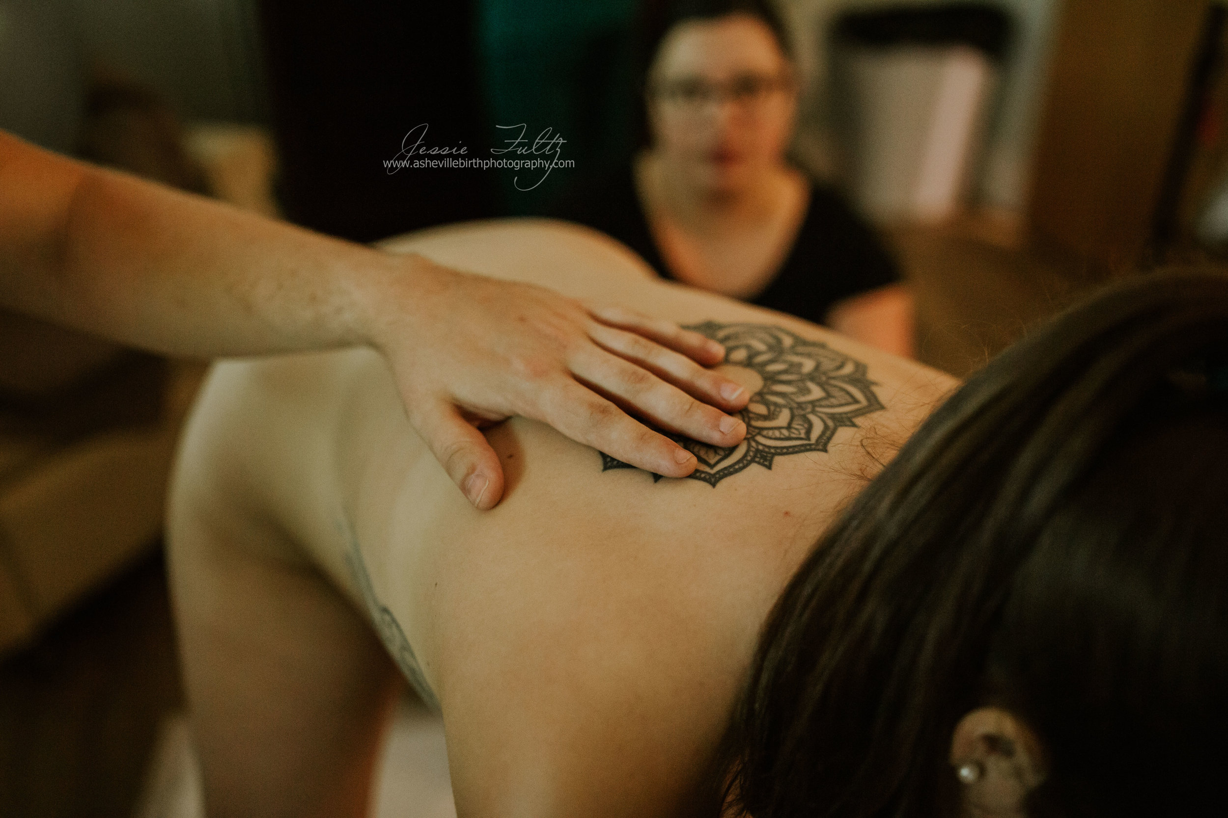 husband's hand on his laboring wife's back with a tribal tattoo