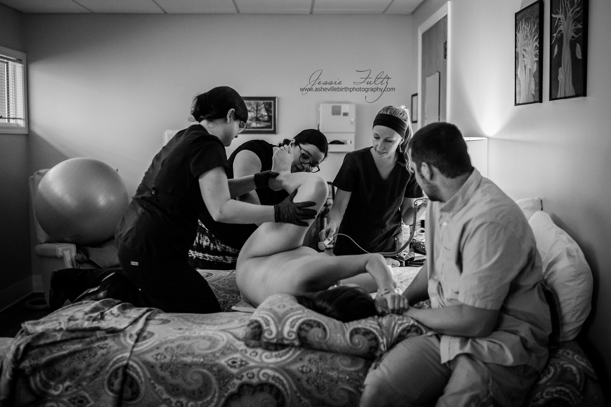 a black and white picture of a woman in labor laying on a bed surrounded by all of her birth team