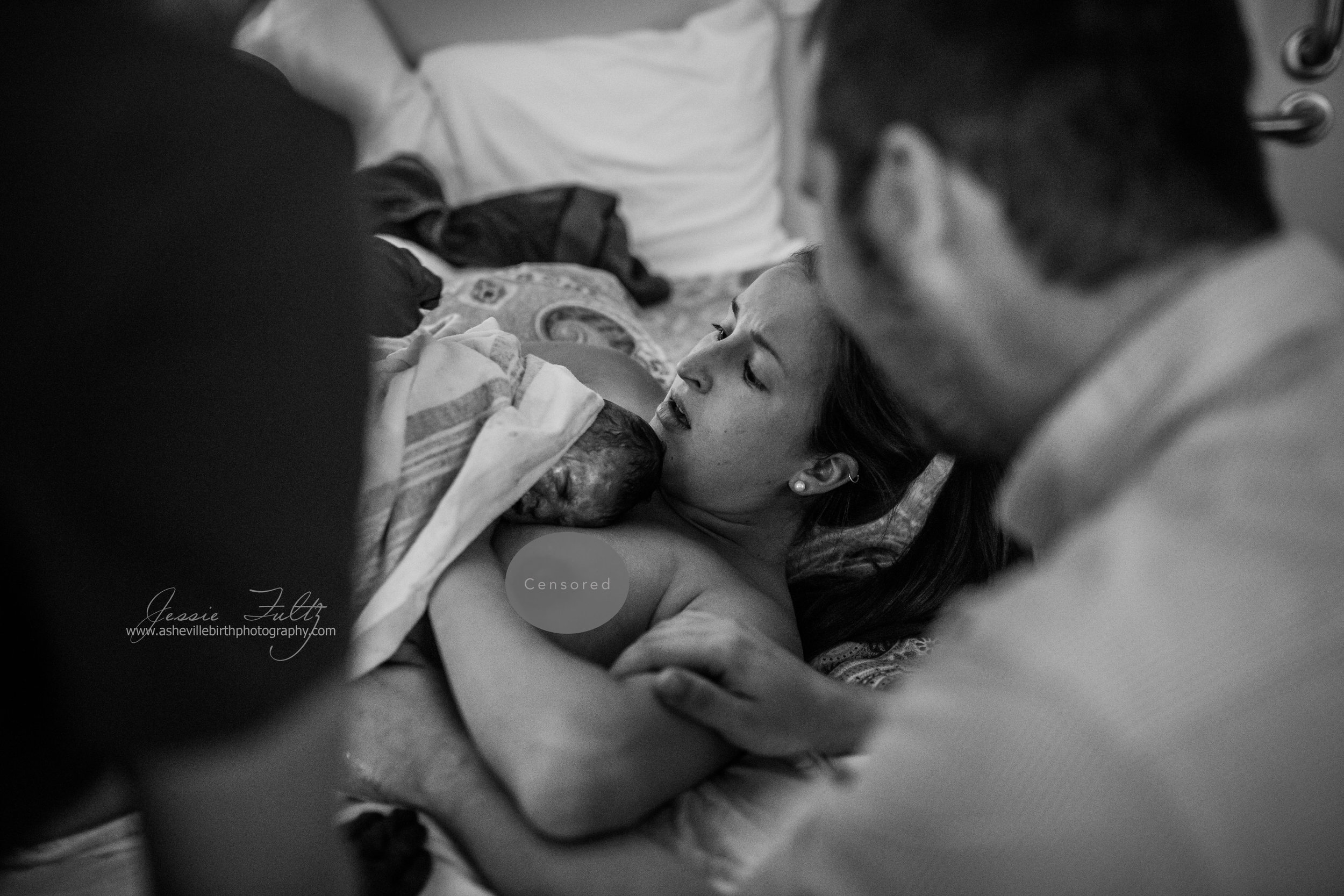 a shocked and emotional new mom looks at her baby whom was just delivered