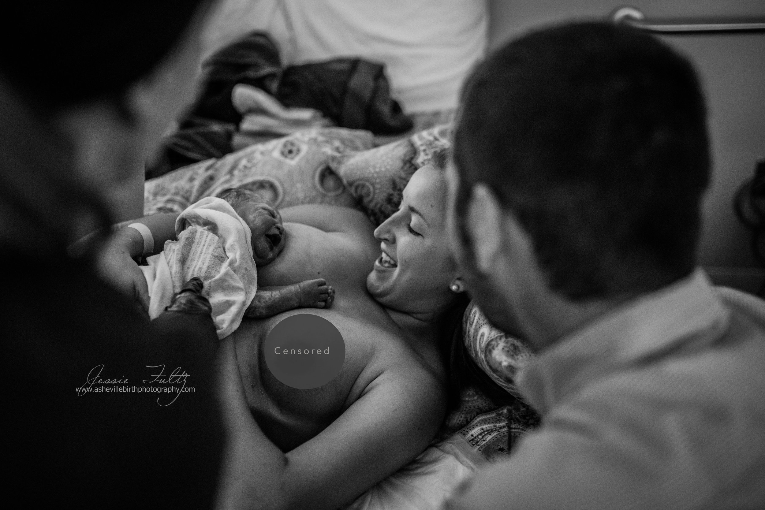 a newborn baby girl on her mom's chest while the woman looks down in joy at her baby