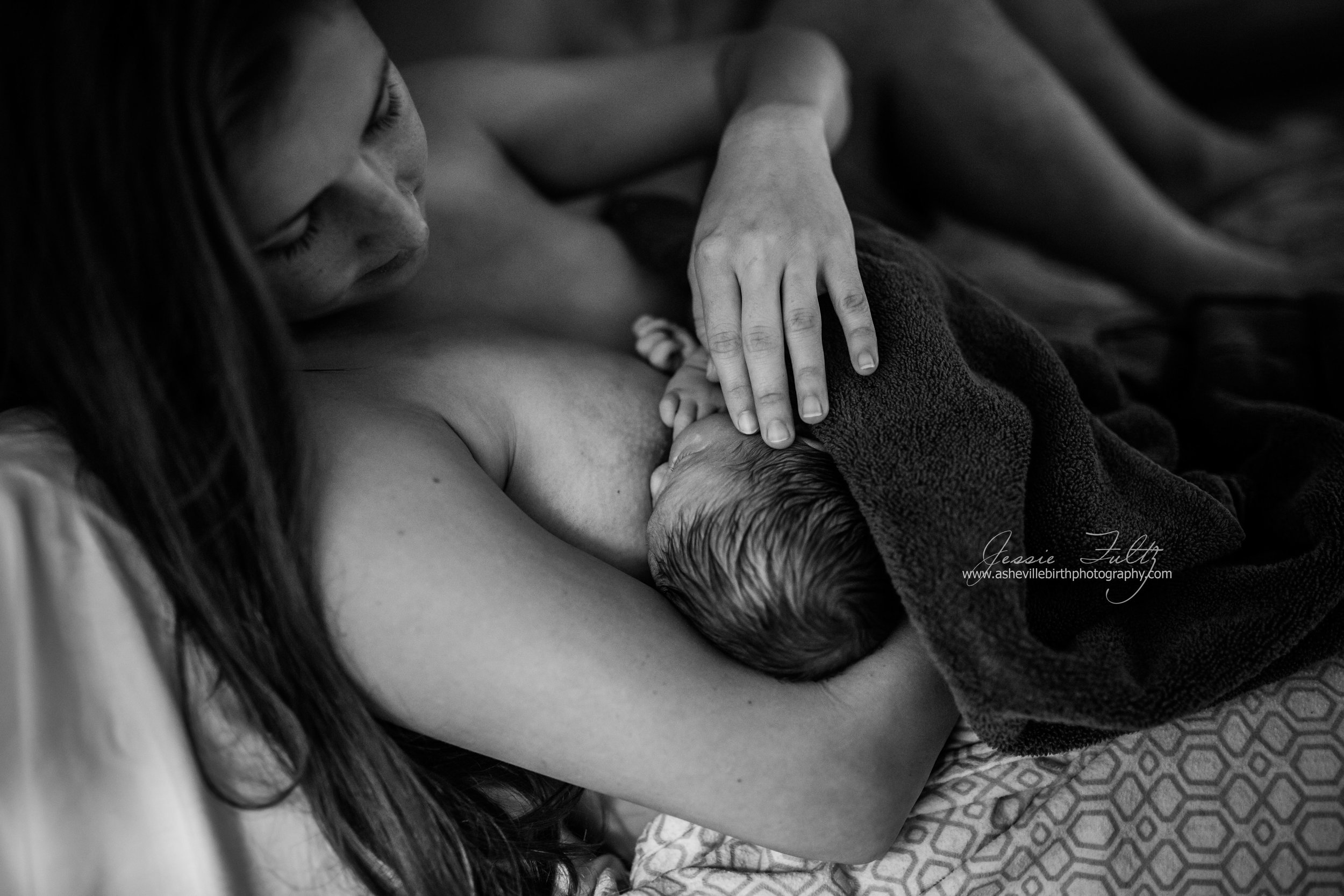 a mother strokes the head of her nursing baby just after birth