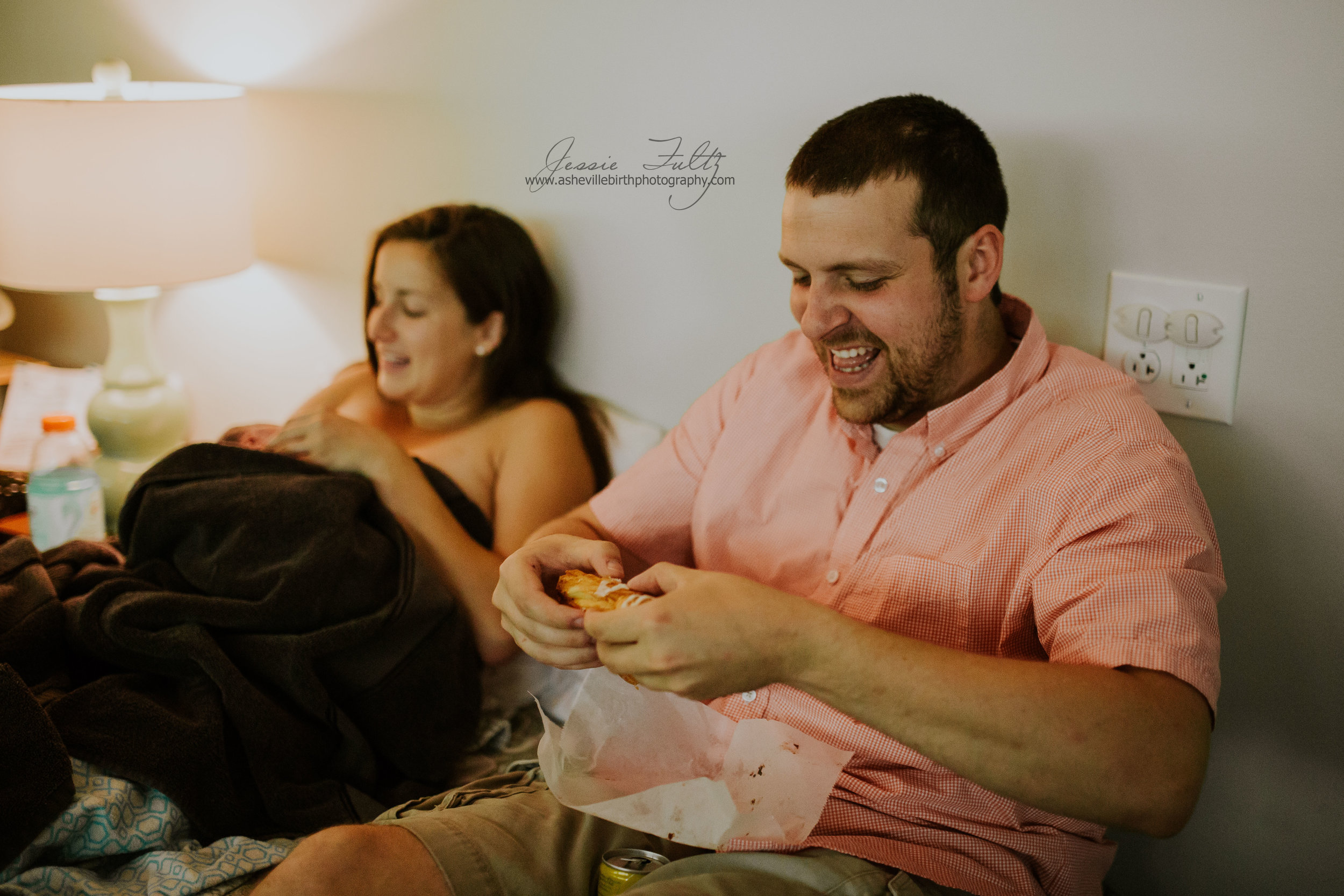 new dad grinning while breaking apart a pastry while his wife nurses their new baby in the background