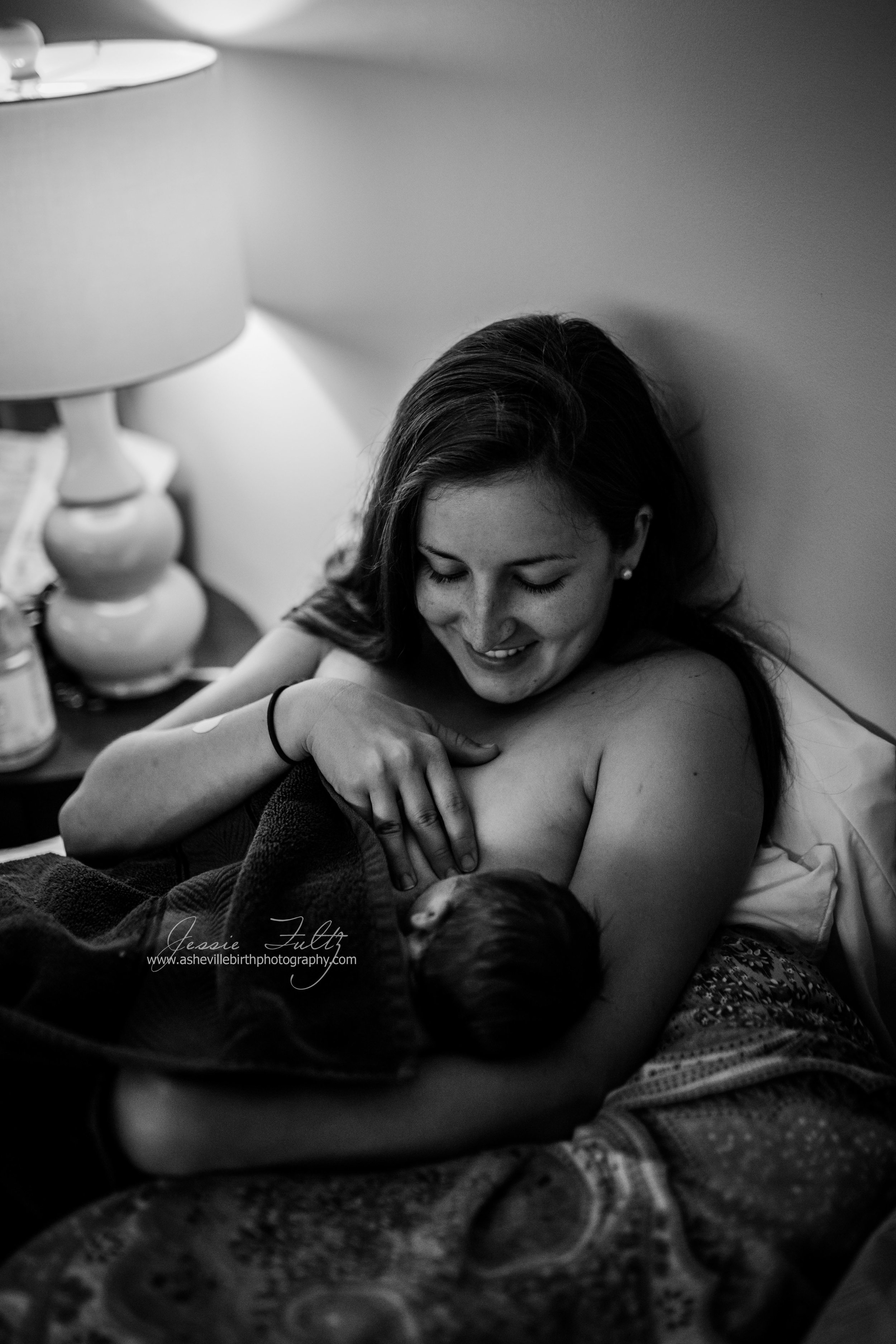 a new mom looking down smiling at her new baby breastfeeding