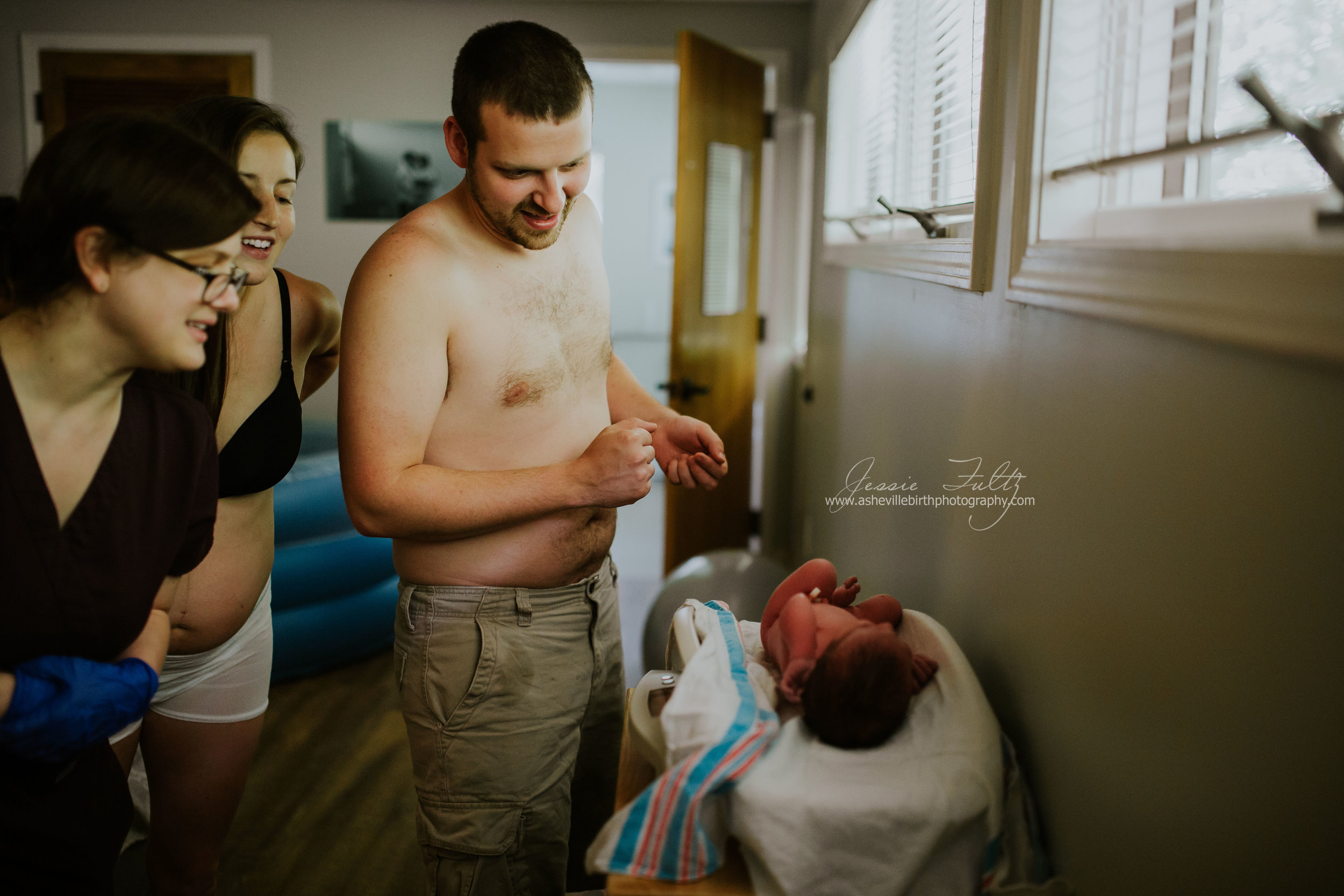 mom dad and midwife watch anxiously as newborn baby is being weighed