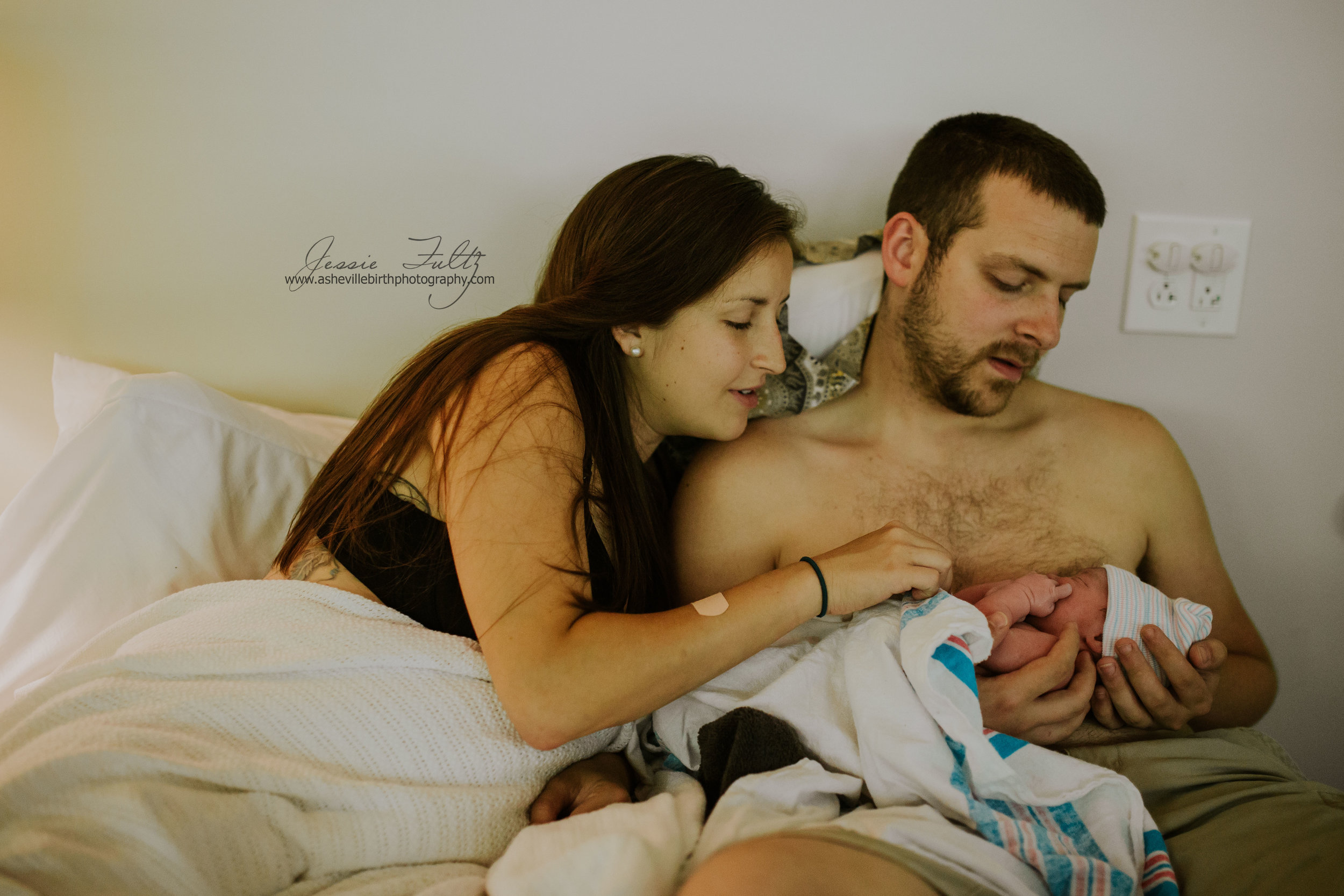 mom and dad sitting in bed with baby just after birth