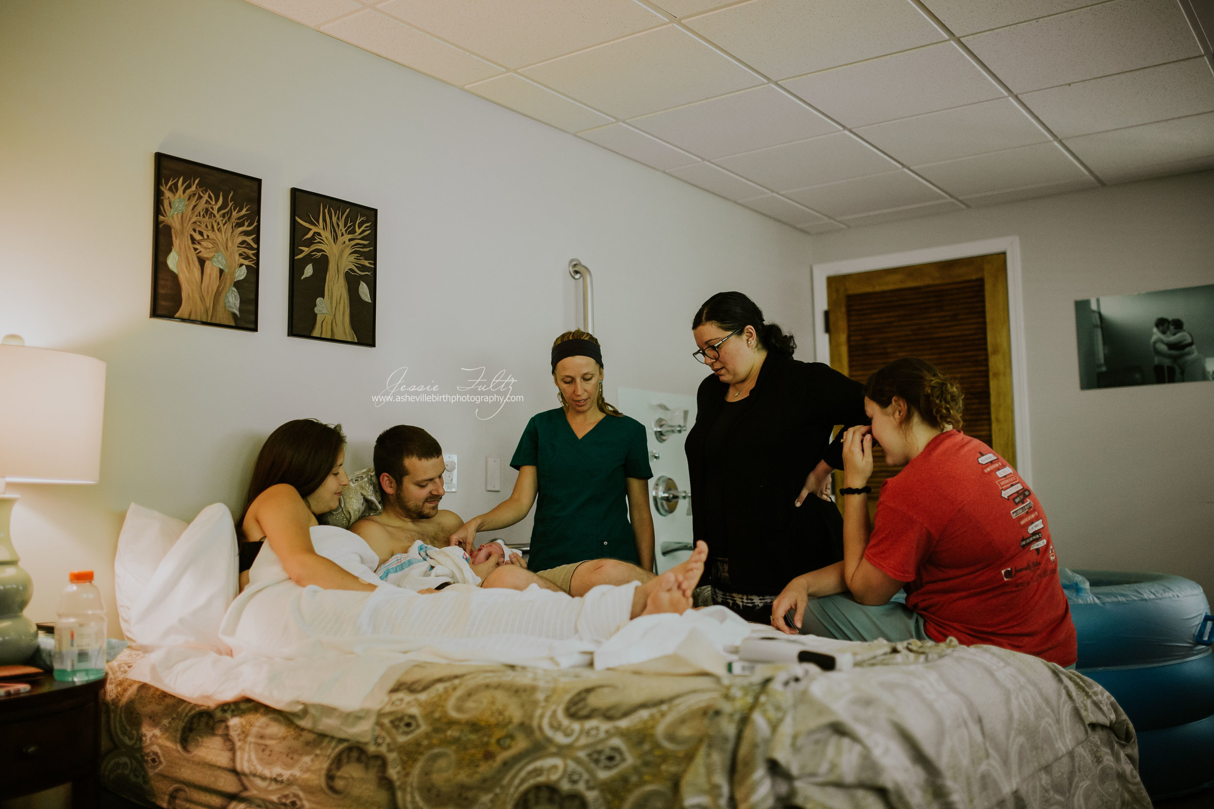 mom and dad sitting in bed with baby just after birth with friend and midwives looking on