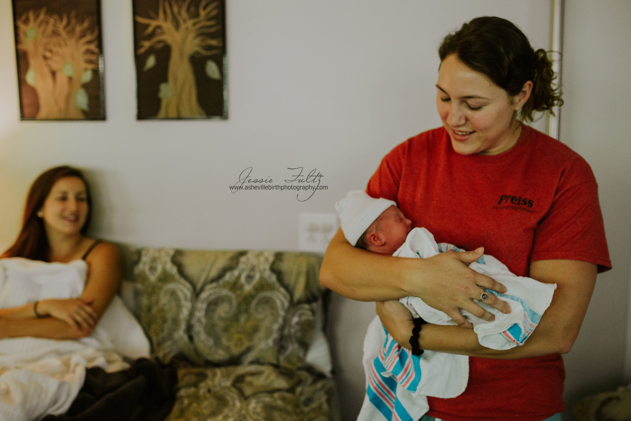 woman holds new baby while mother looks on in the background