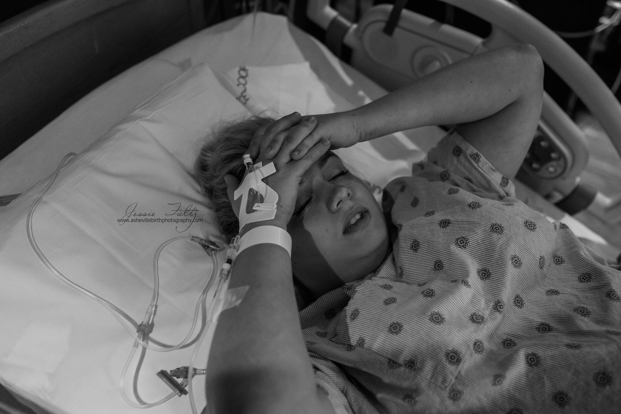 a laboring woman clasping her hands and resting them on her forehead during a contraction