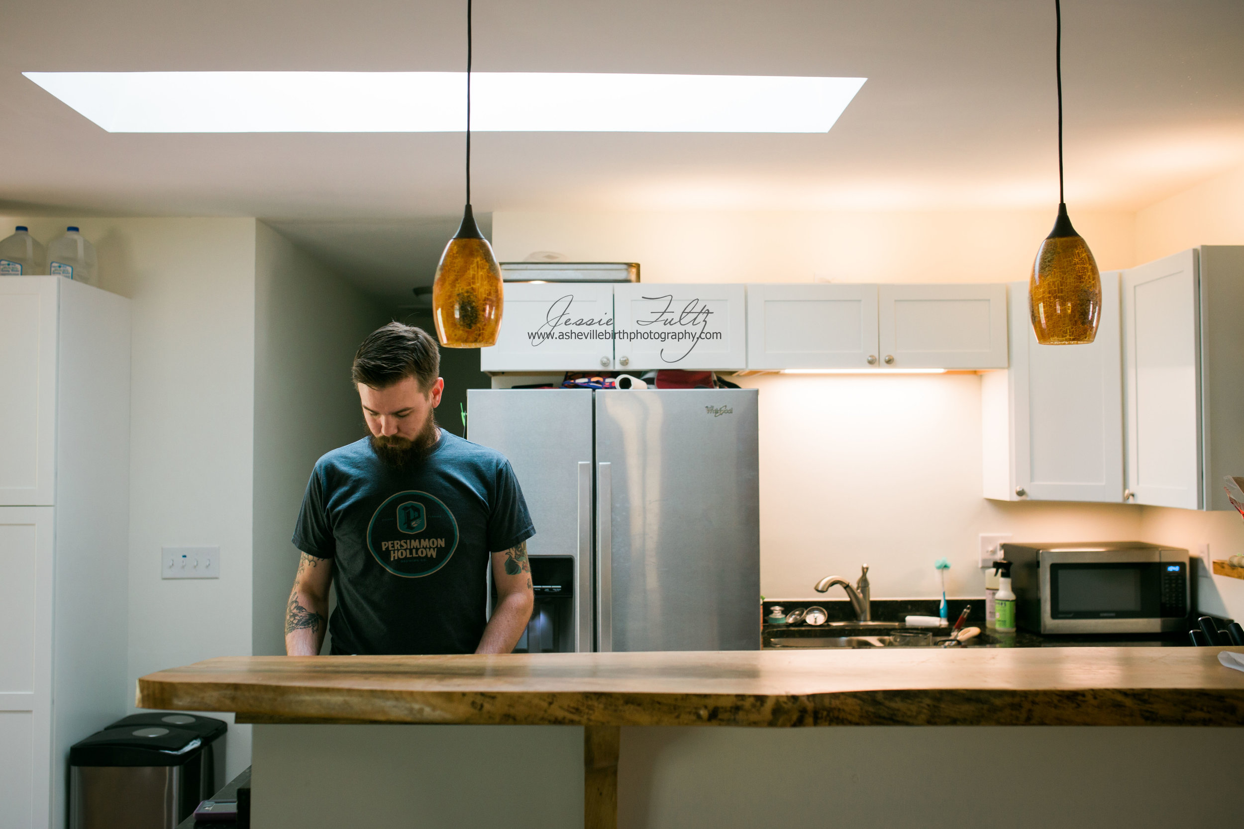 man in black t-shirt standing behind wooden-top bar in kitchen