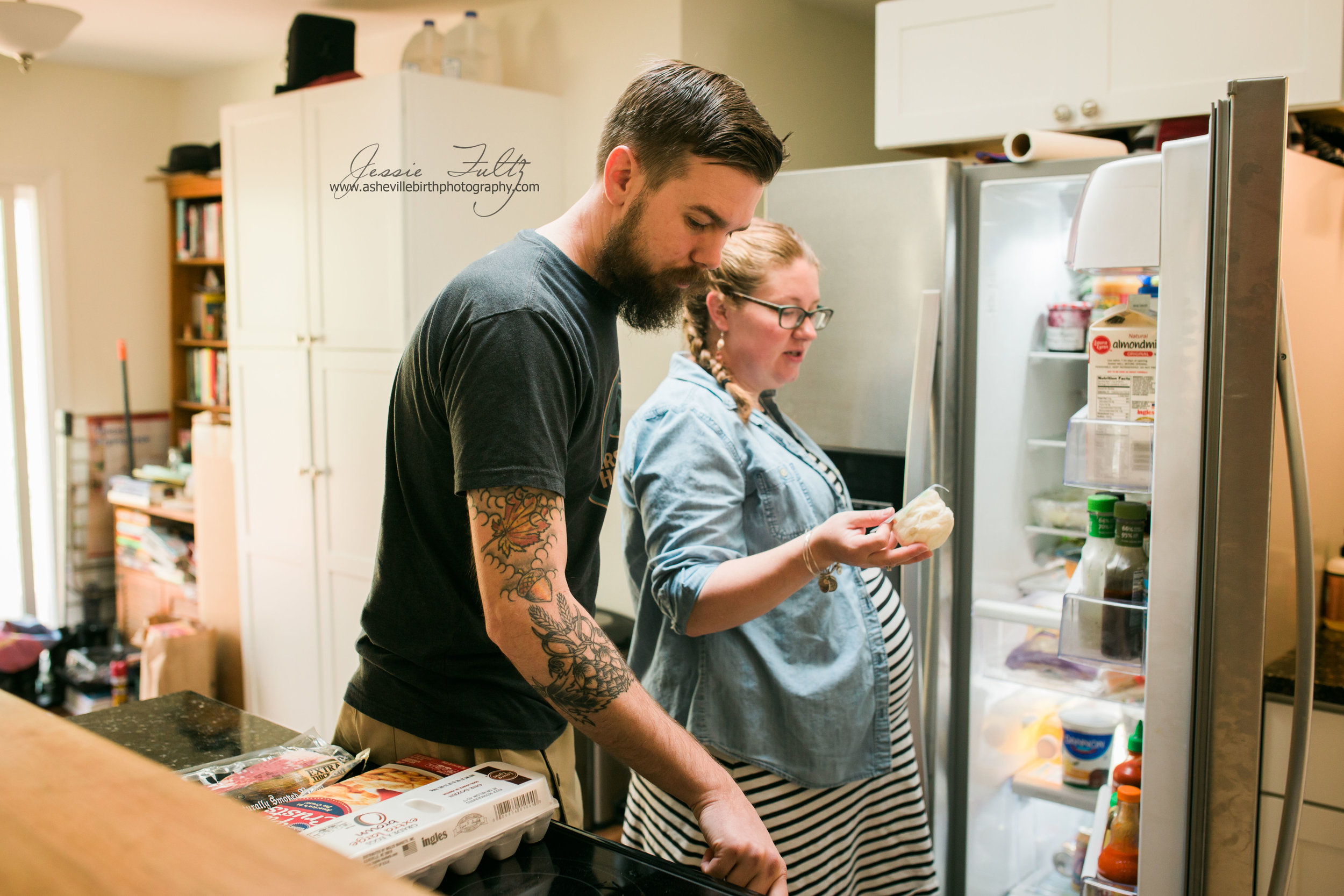 pregnant woman and husband standing in front of the refrigerator